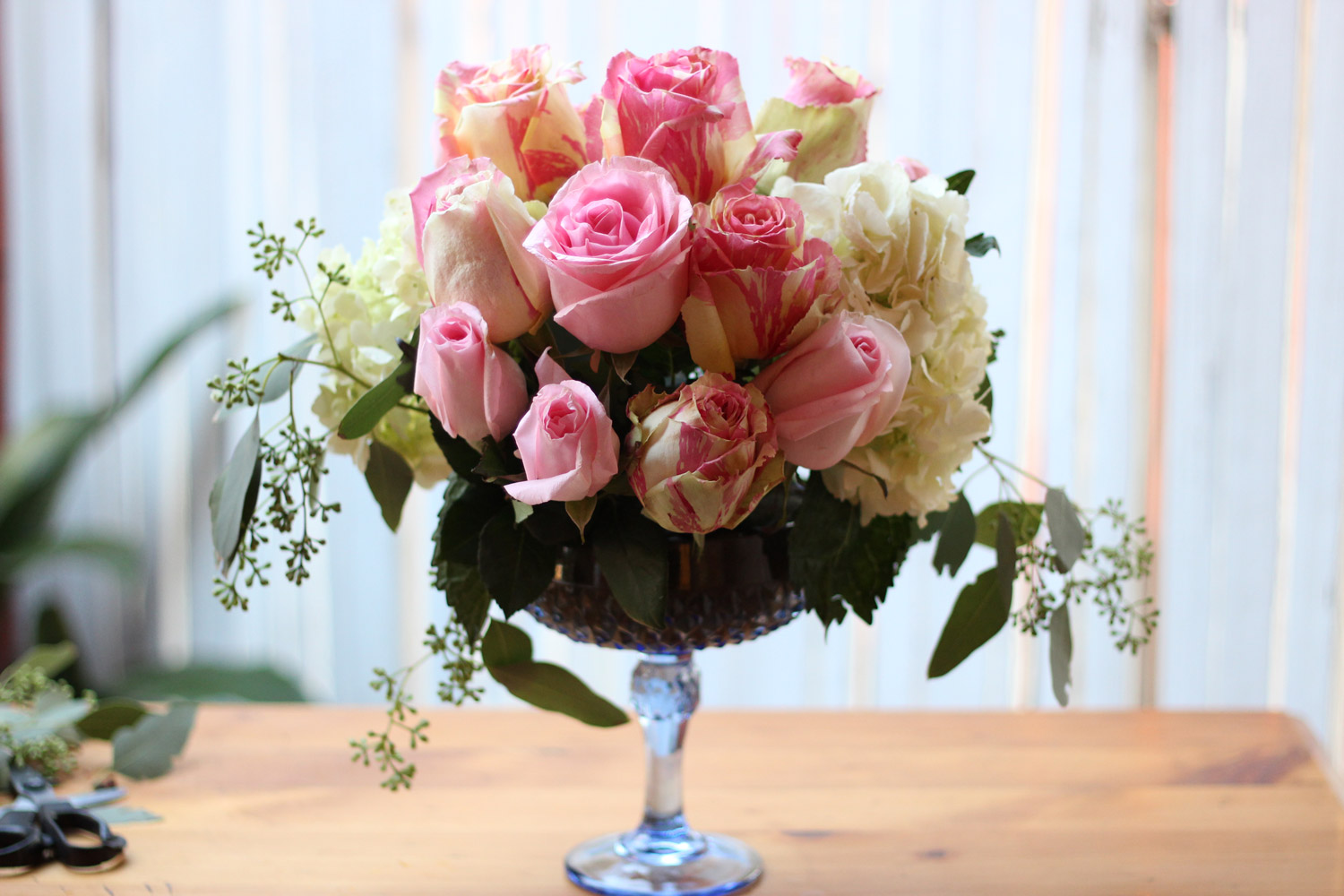 Cut roses shorter as you go, so arrangement is rounded.