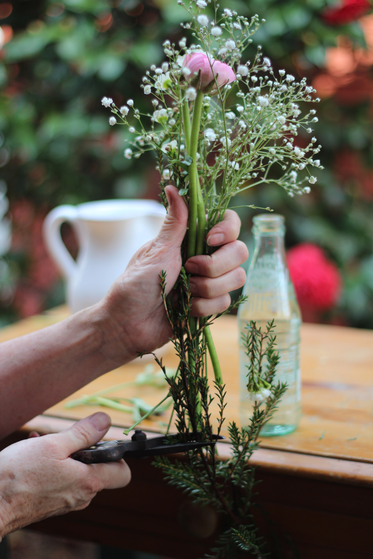 Add baby's breath. It should be2 inches higher. Add wax flowers at same height as the ranunculus. Cut stems. Strip leaves below water line.