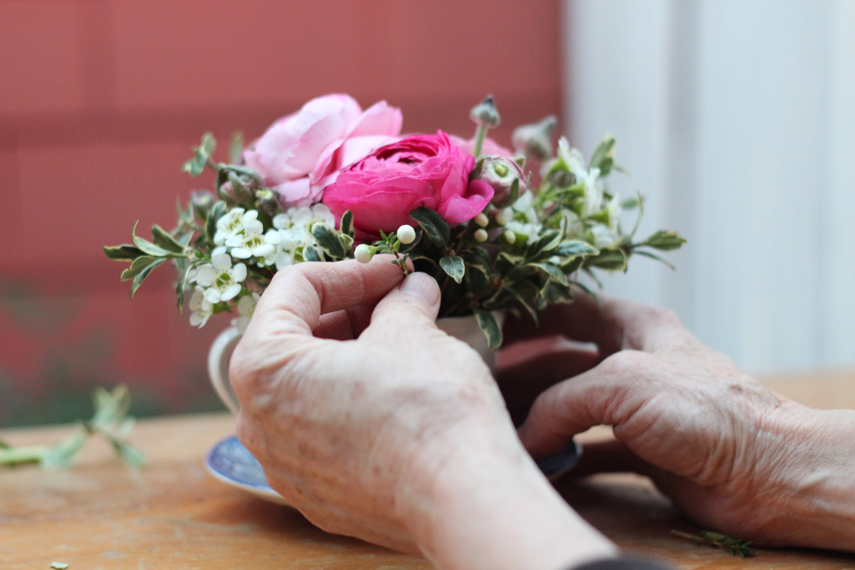 Place wax flower buds into the arrangement.