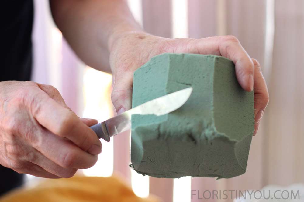 Shape bottom of foam to fit vase.
