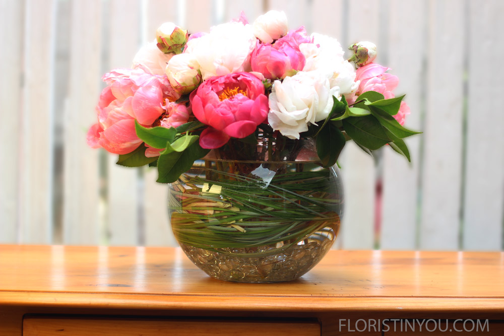 Arrange rest of blooms in back with large bloom for focal point, low in center.