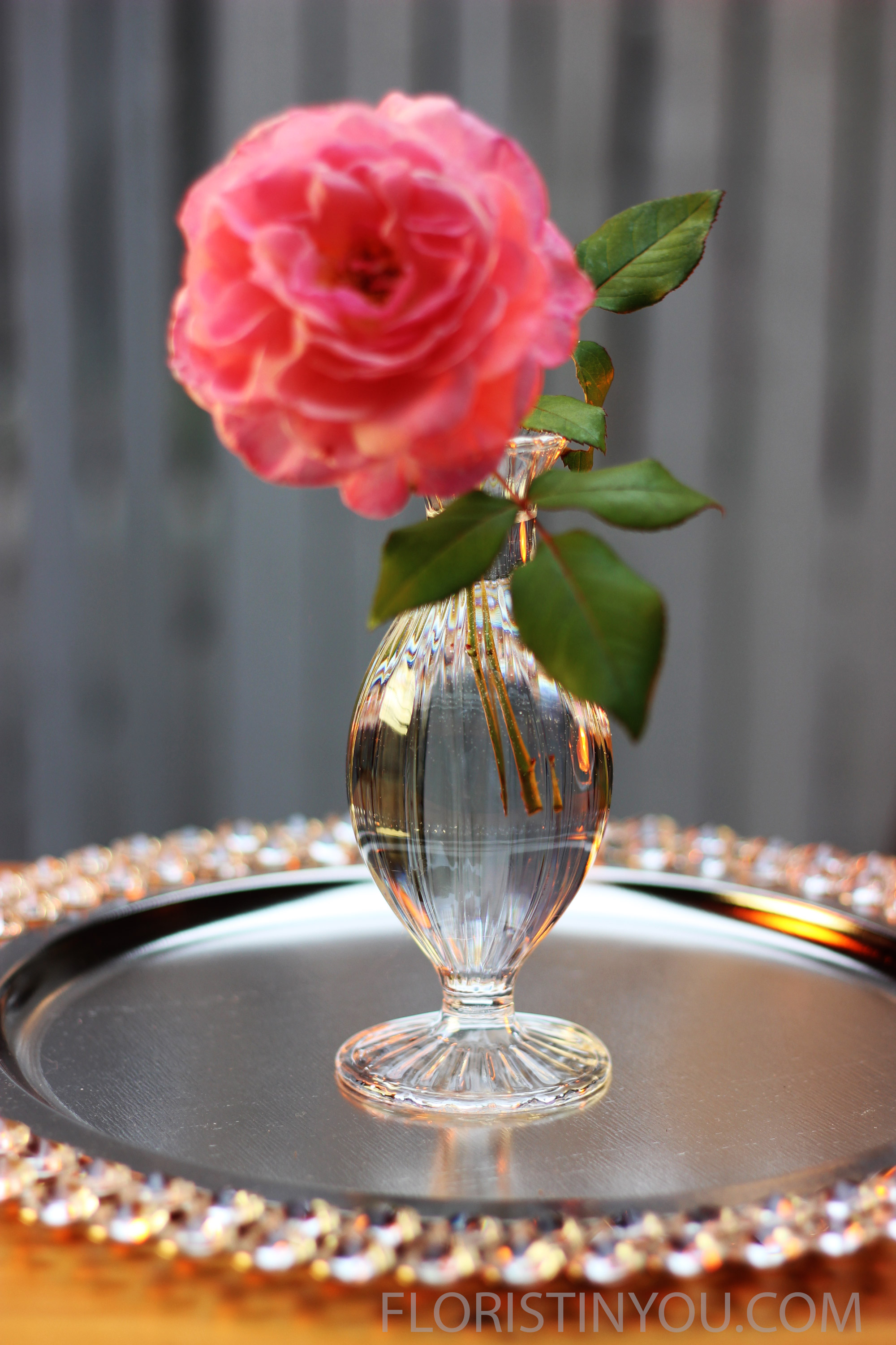 A short bloom goes in the smallest vase in the front.