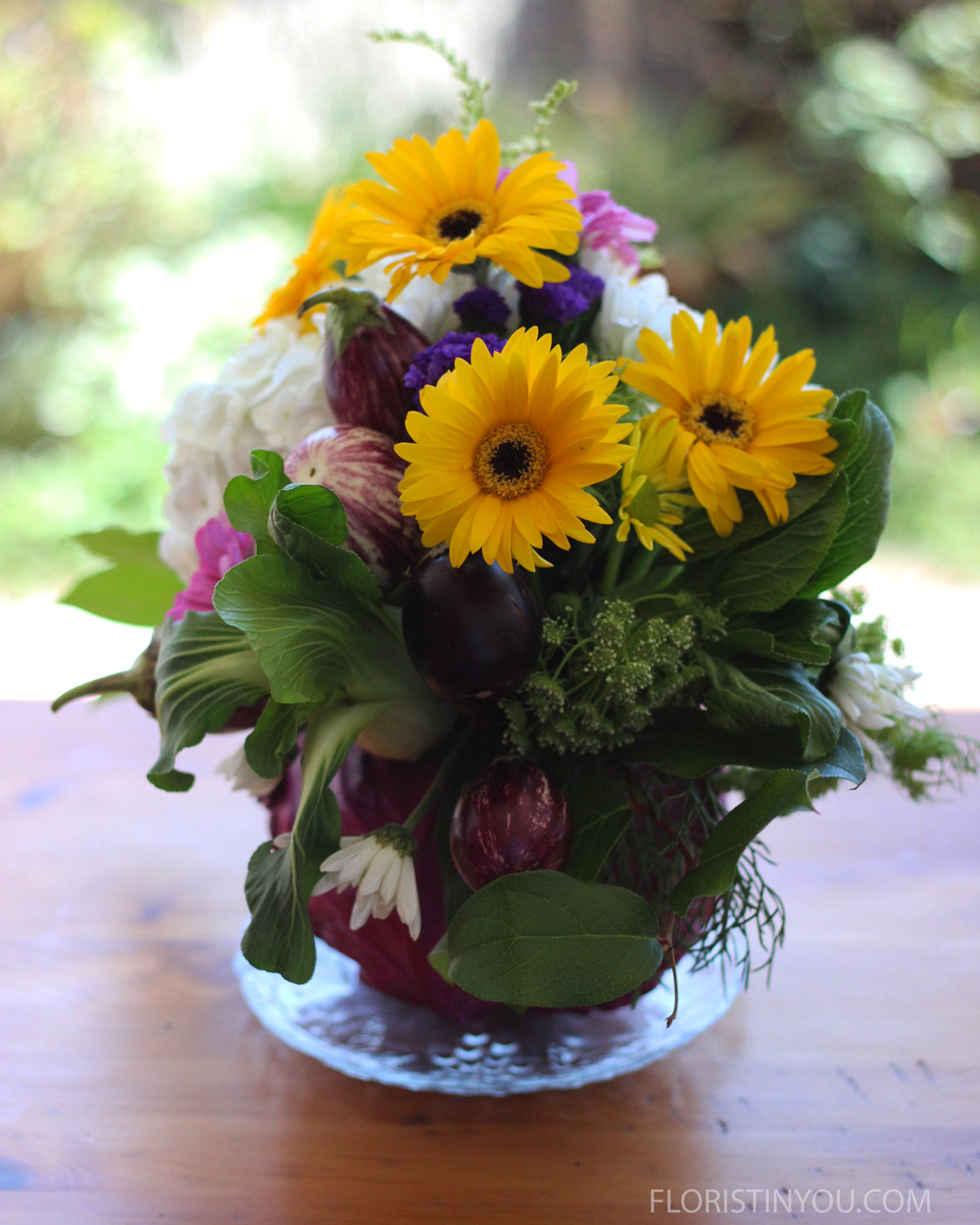 Put some of the yellow Gerbers and purple Cosmos down the center line of the arrangement. The side should look like this.