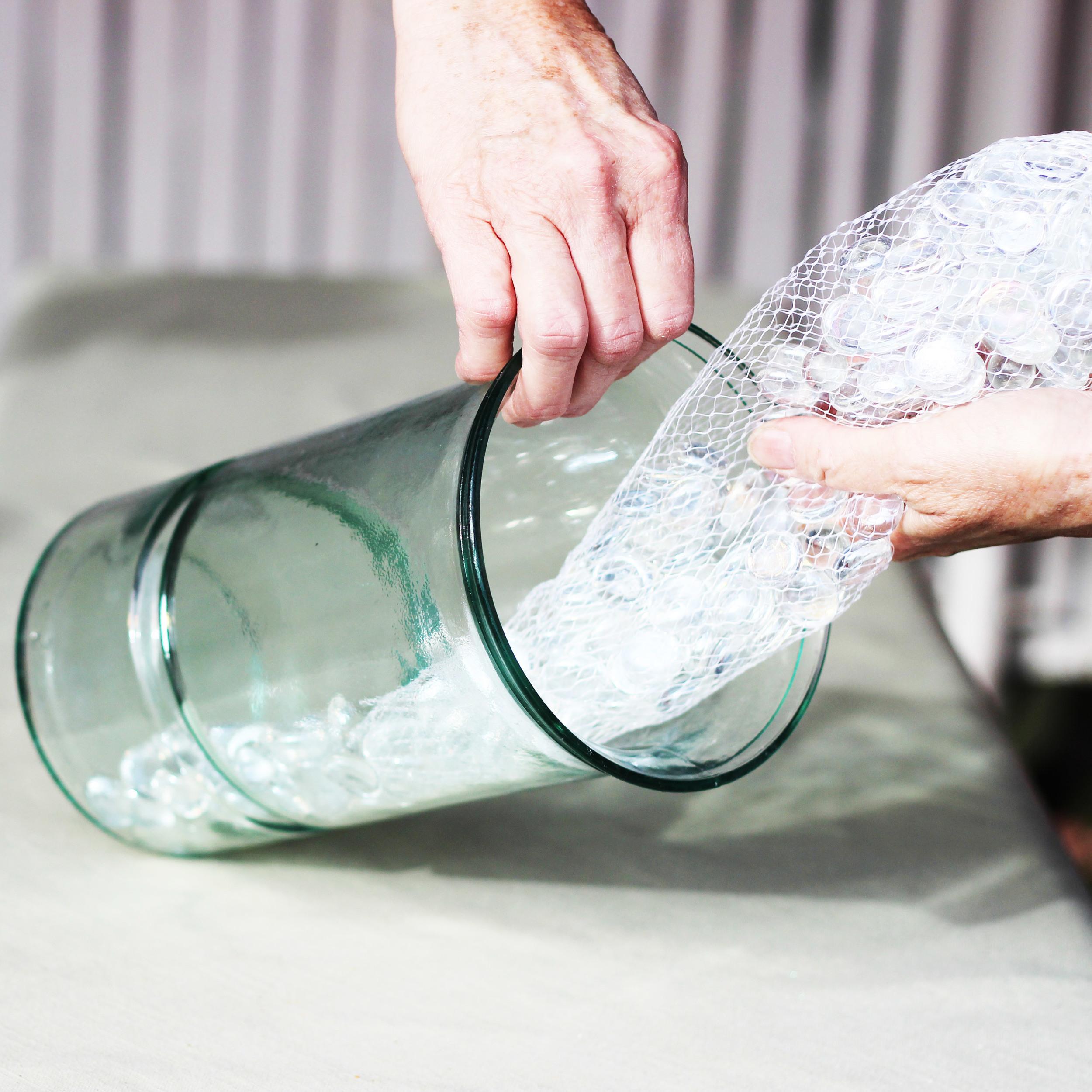 Tilt vase on side and gently slide marbles in.