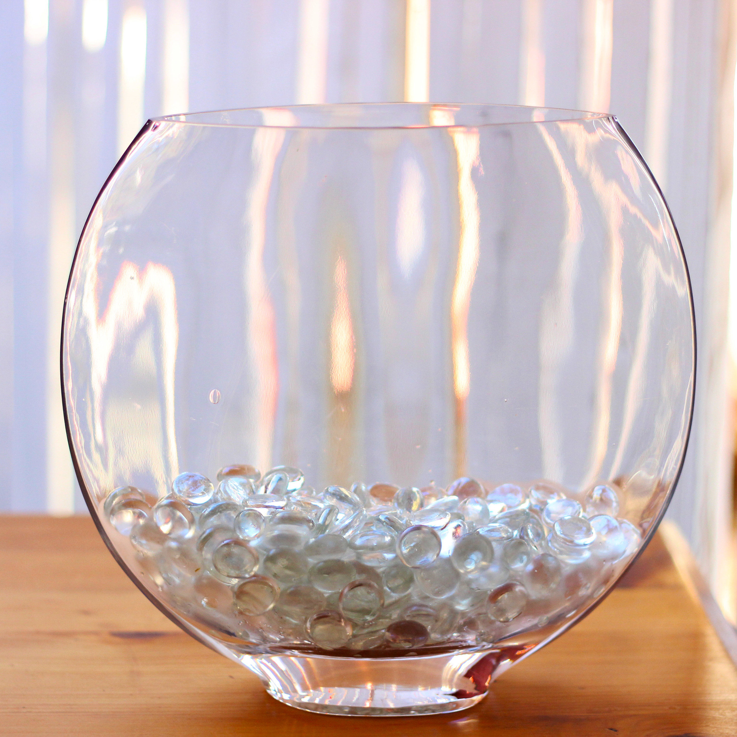 Carefully slide marbles into the bottom of the vase.