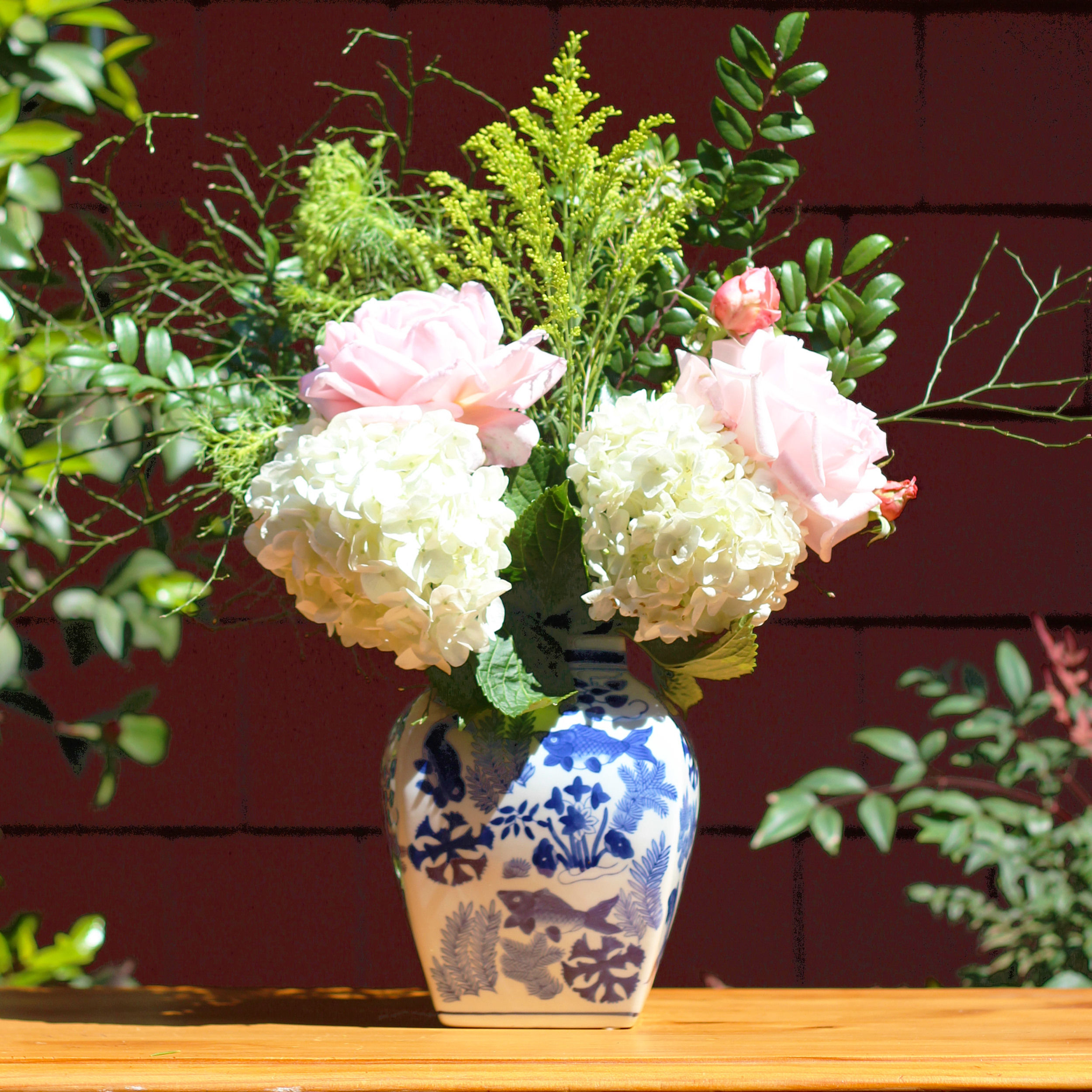 Put one hydrangea low on each side and one pink rose above in the front.