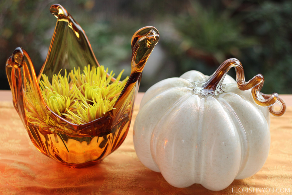 Float the Spider Mums in the vase and add one white pumpkin.