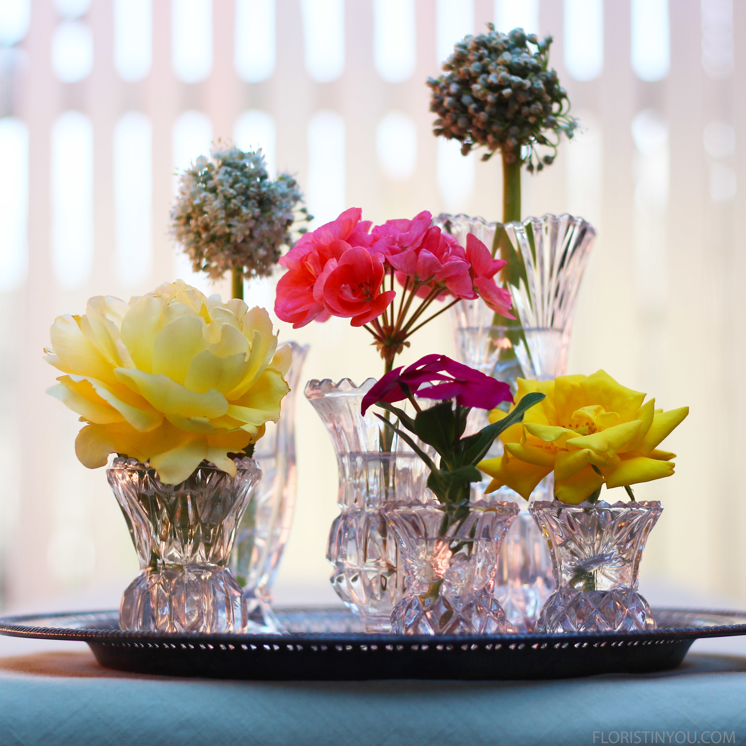 Have some variations in the height of the vases and blooms, as well as repetition of bloom types and colors. Put them on a silver tray and you are done. Have a fun dinner party.