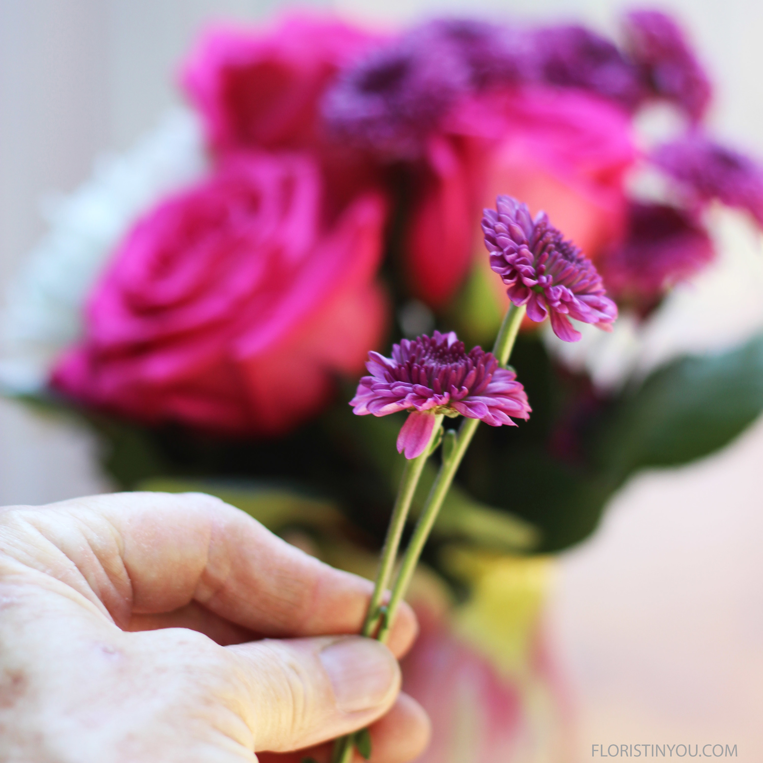 Put flowers in vase. Then add shorter flowers you saved in the front.