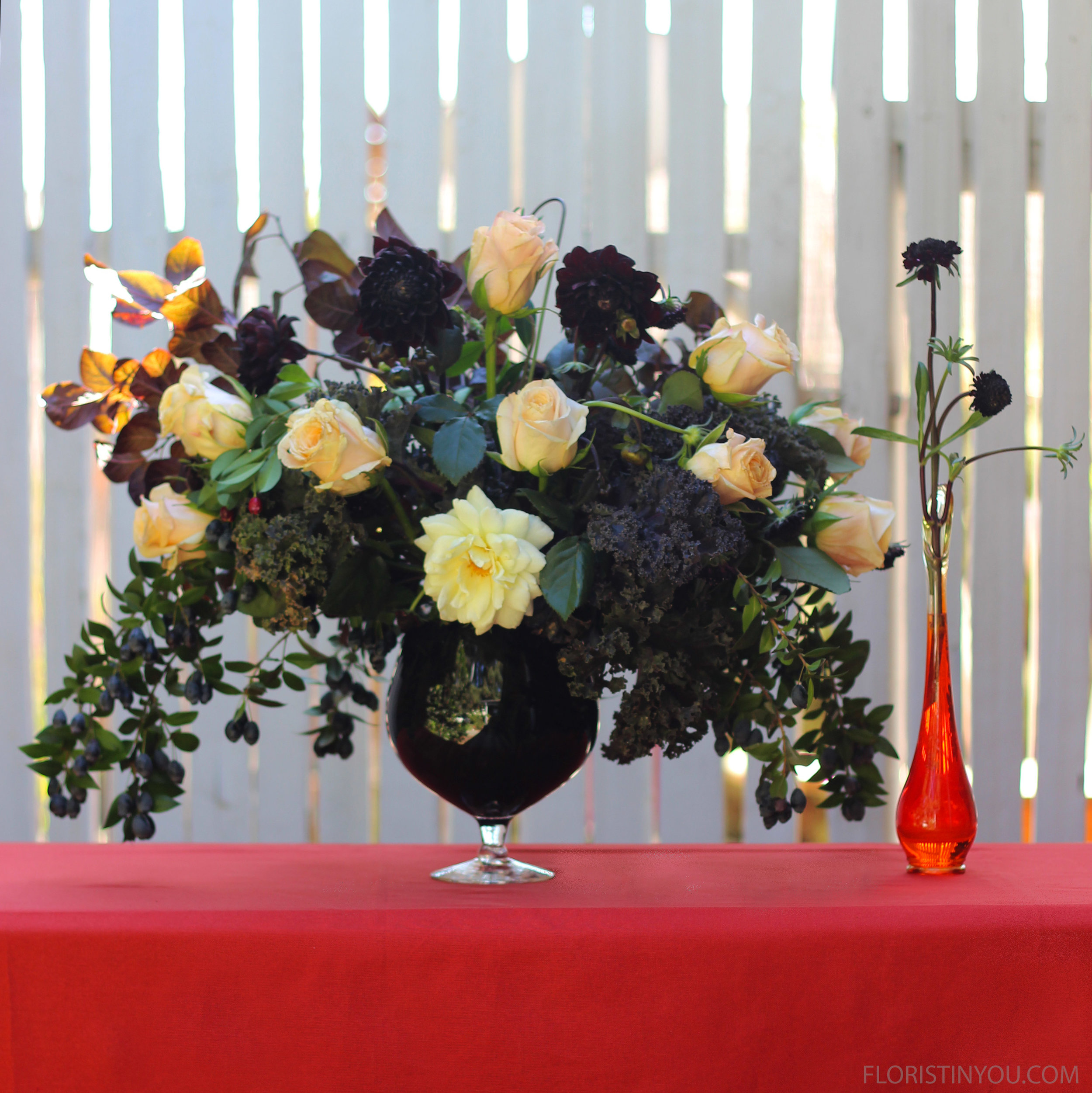The orange hand blown bud vase compliments the 'black glass' of the arrangement.