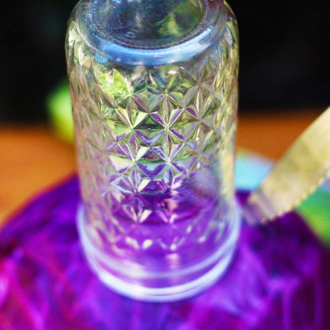 Take a jar with a mouth slightly larger than the tapered glass and cut around its edges.