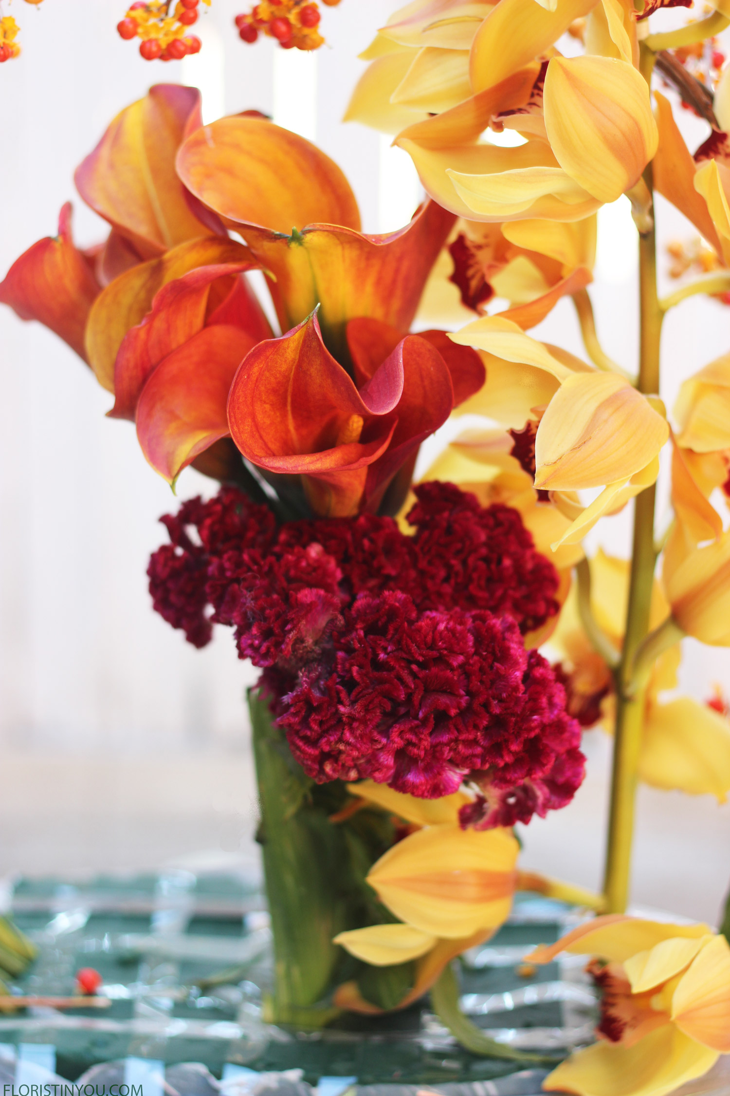 Cut 2 Burgundy Celosia. Insert in front of Calla Lilies; one in front and one in back.