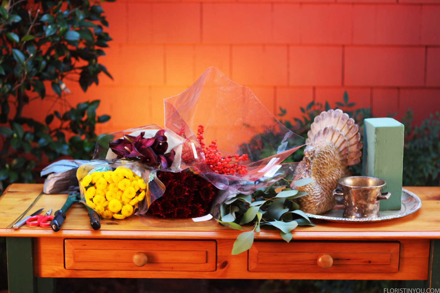 Here are your mums, Calla Lilies, Ilex Berries, and Eucalyptus Leaves, wooden turkey, silver cup, foam, and tools.