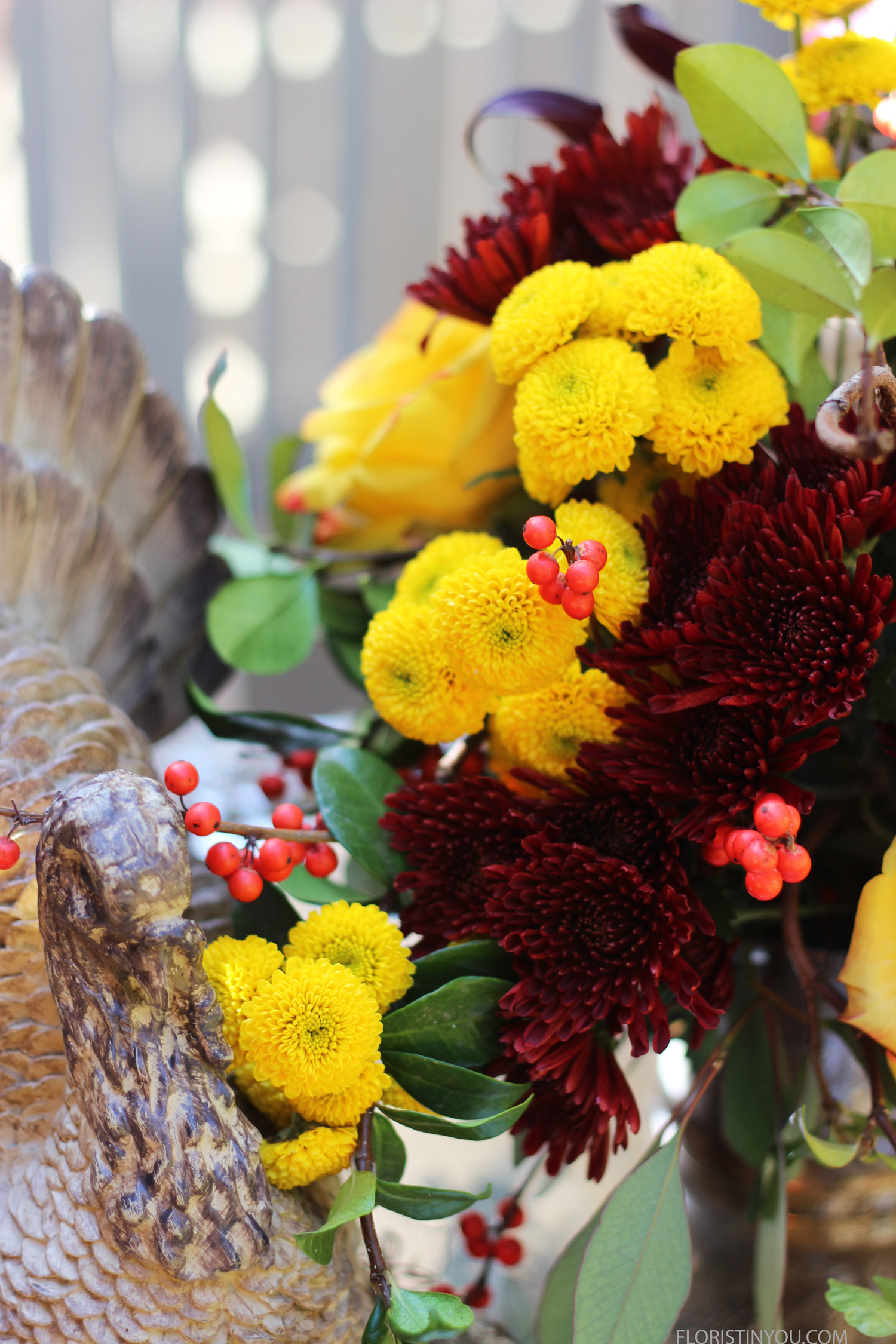 A wooden Turkey nestles in the mums.