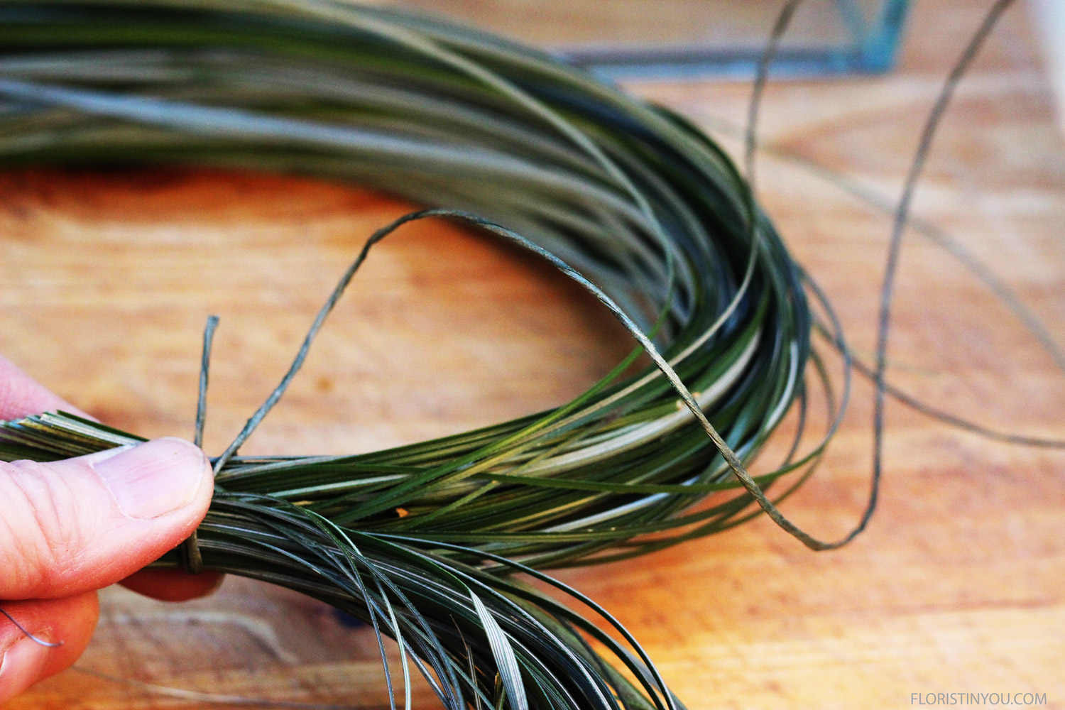 Bring tips grass into heart shape. Bind leaving 1.5 inch loose end. Wrap once. Pull tight and double knot. Wrap 3 more times. Pull tight. Double knot. Wrap ends around. Trim ends grass.