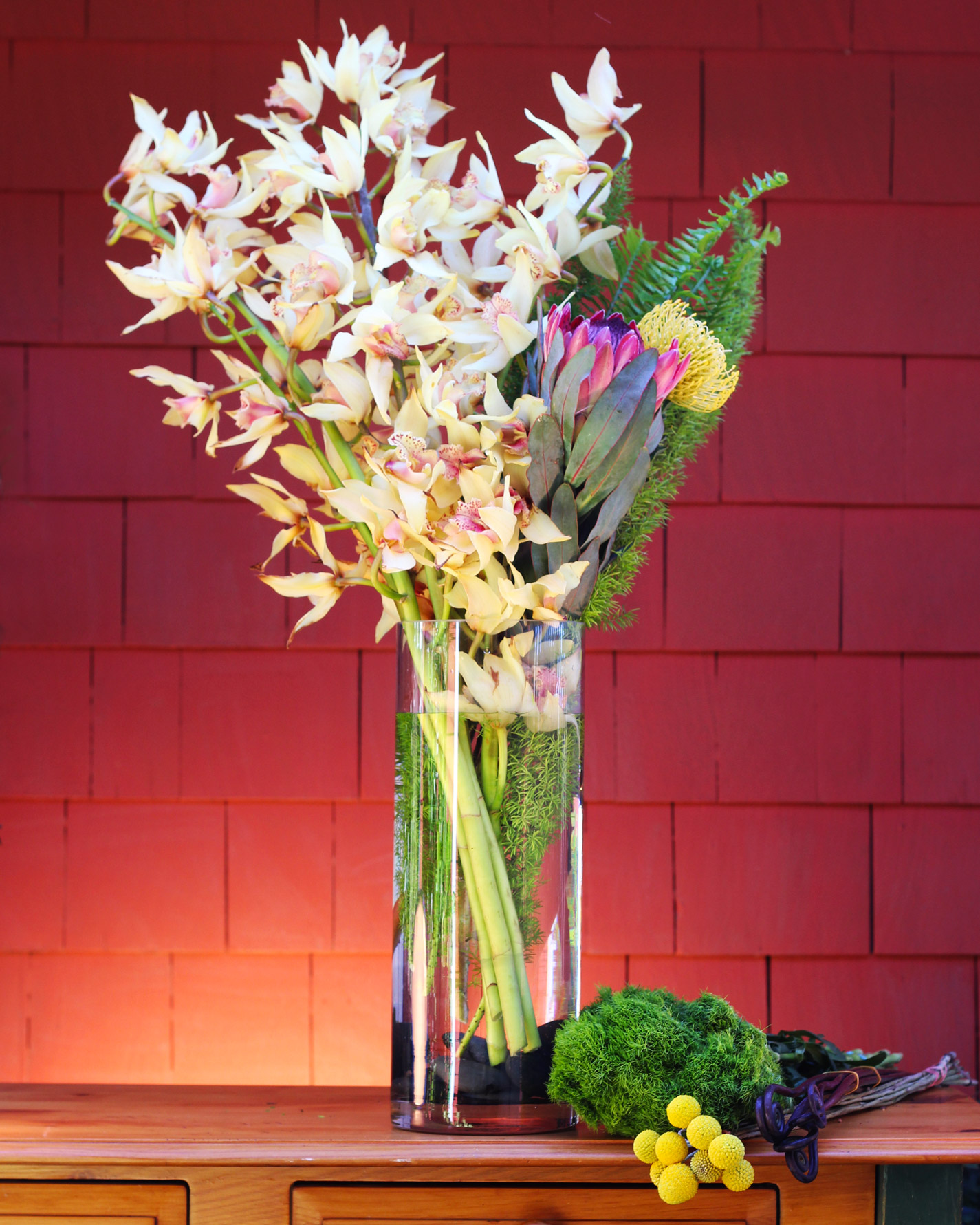 Put orchids left to center with ferns, Protea & Pincushion on right.