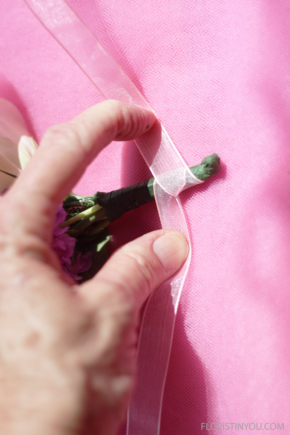 Place corsage in middle of ribbon. Wrap by crossing ribbon, wrapping, crossing, etc.