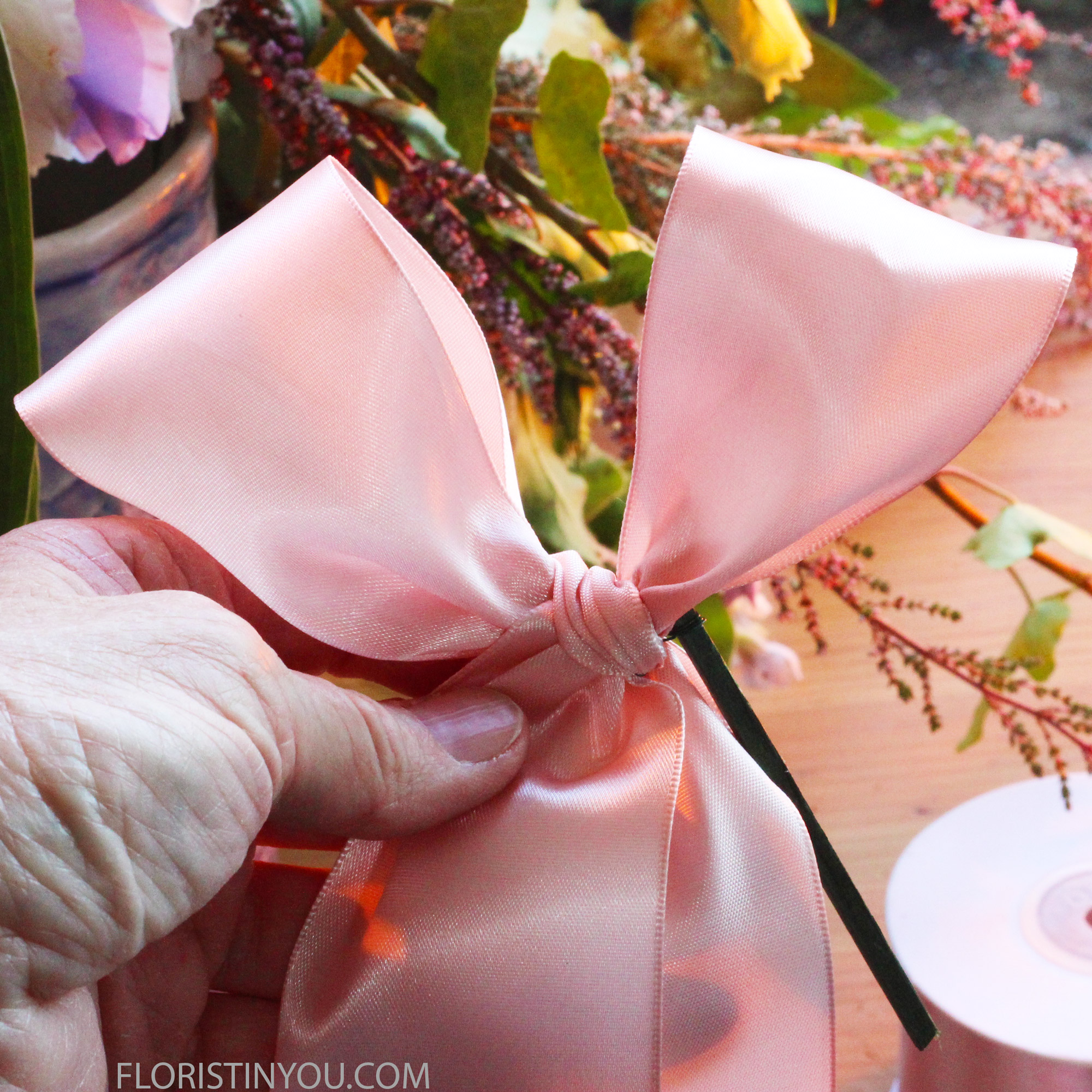 Tie a bow. Cut ends at 45 degrees. Insert pick into bouquet holder.