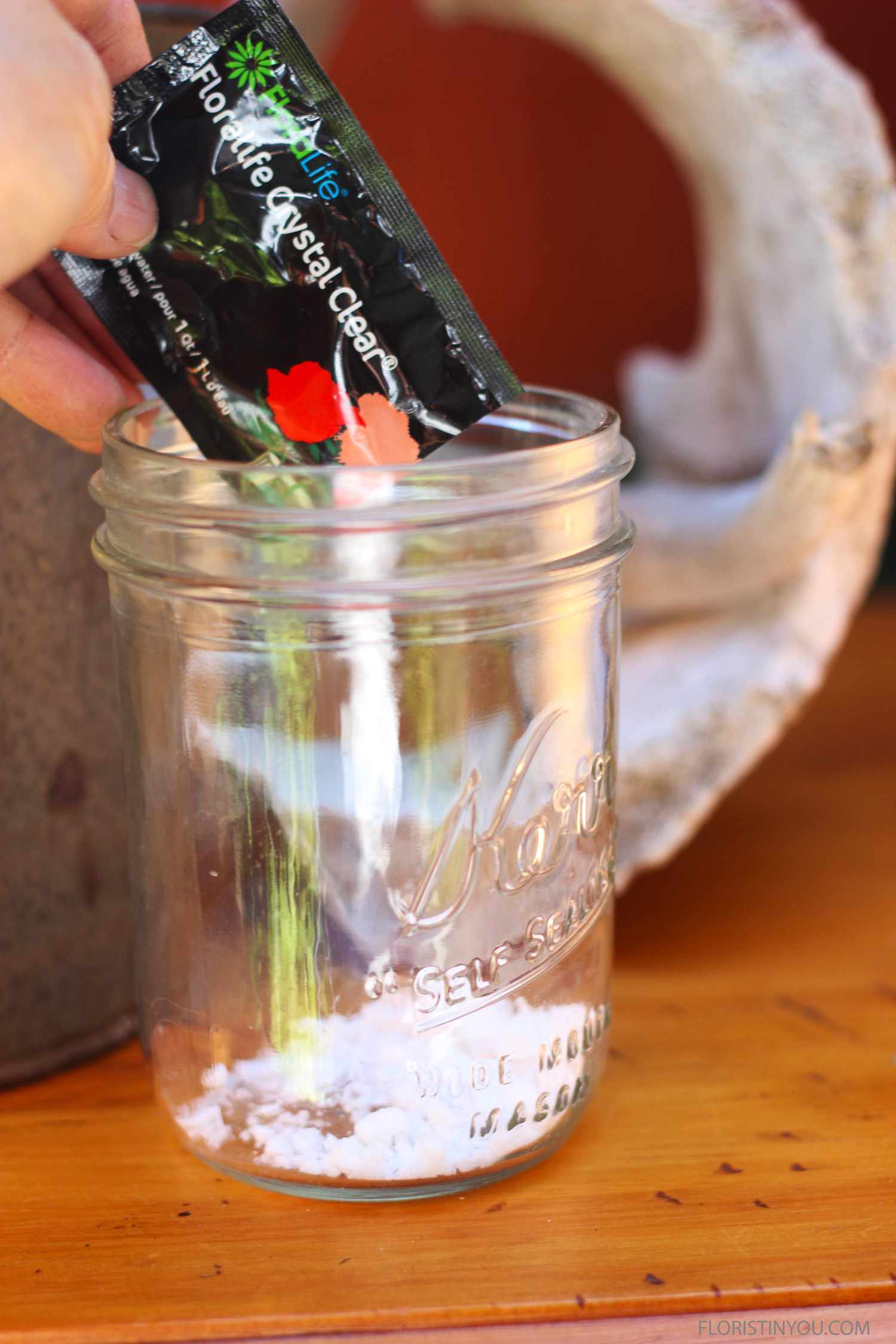 Put a package of flower food into a mason jar.