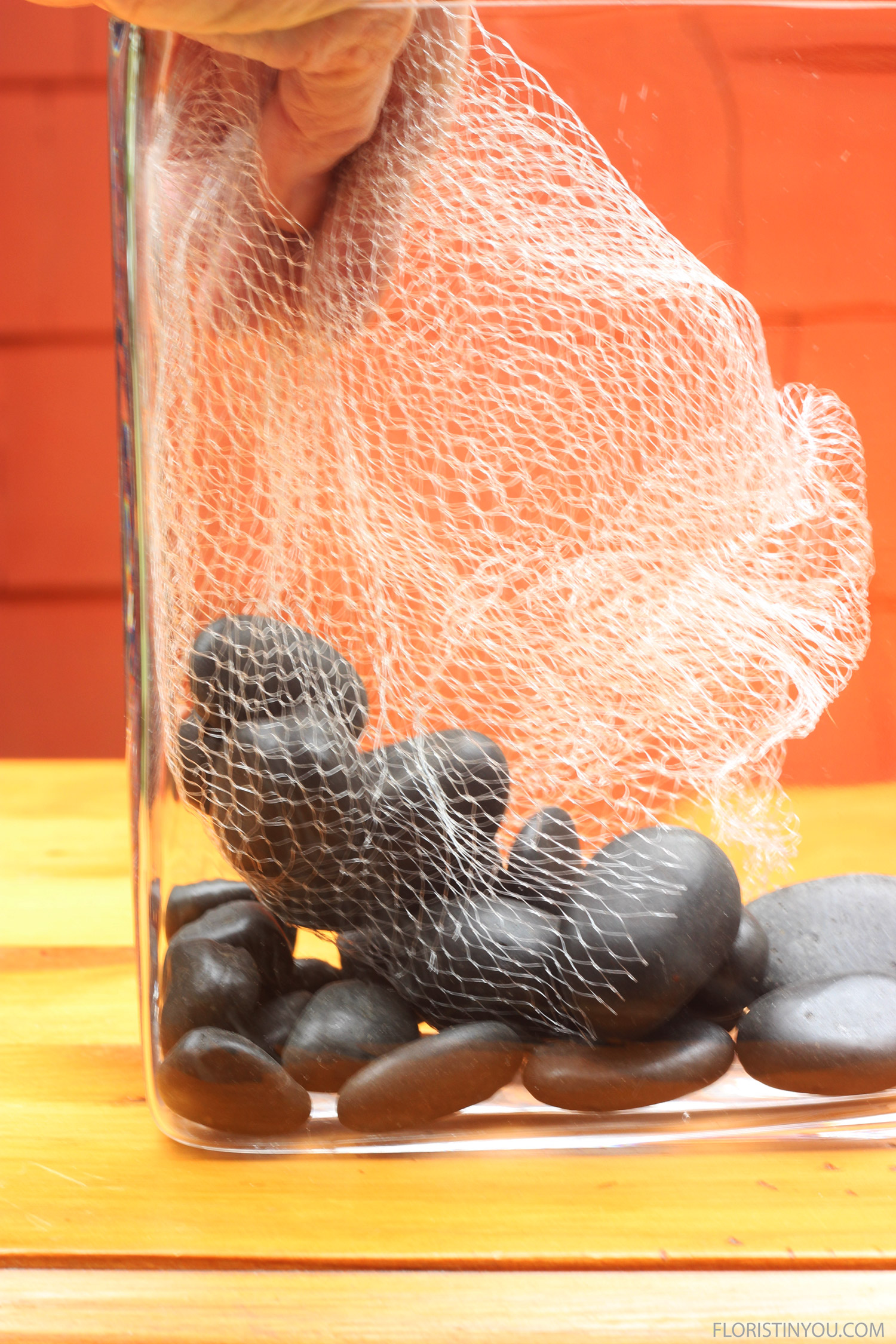 Carefully lower bag of large river rocks into vase.