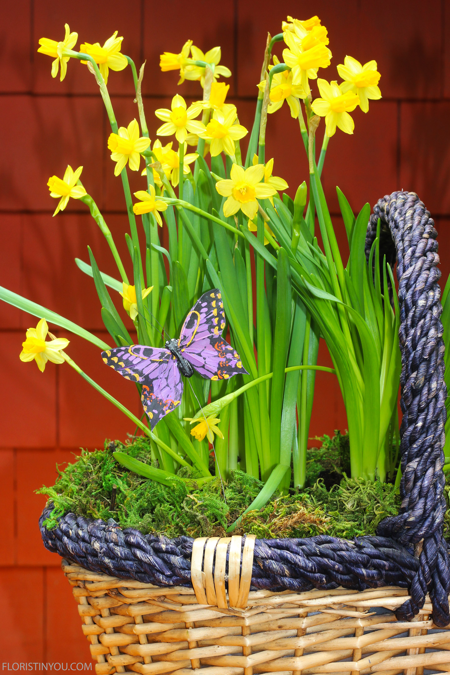 Stick purple butterfly wire through moss into dirt on left side of basket.