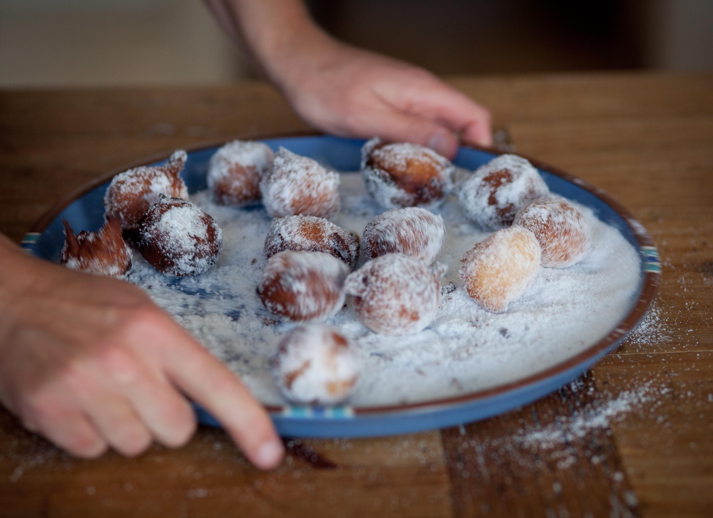 Rolling the doughnut balls in sugar