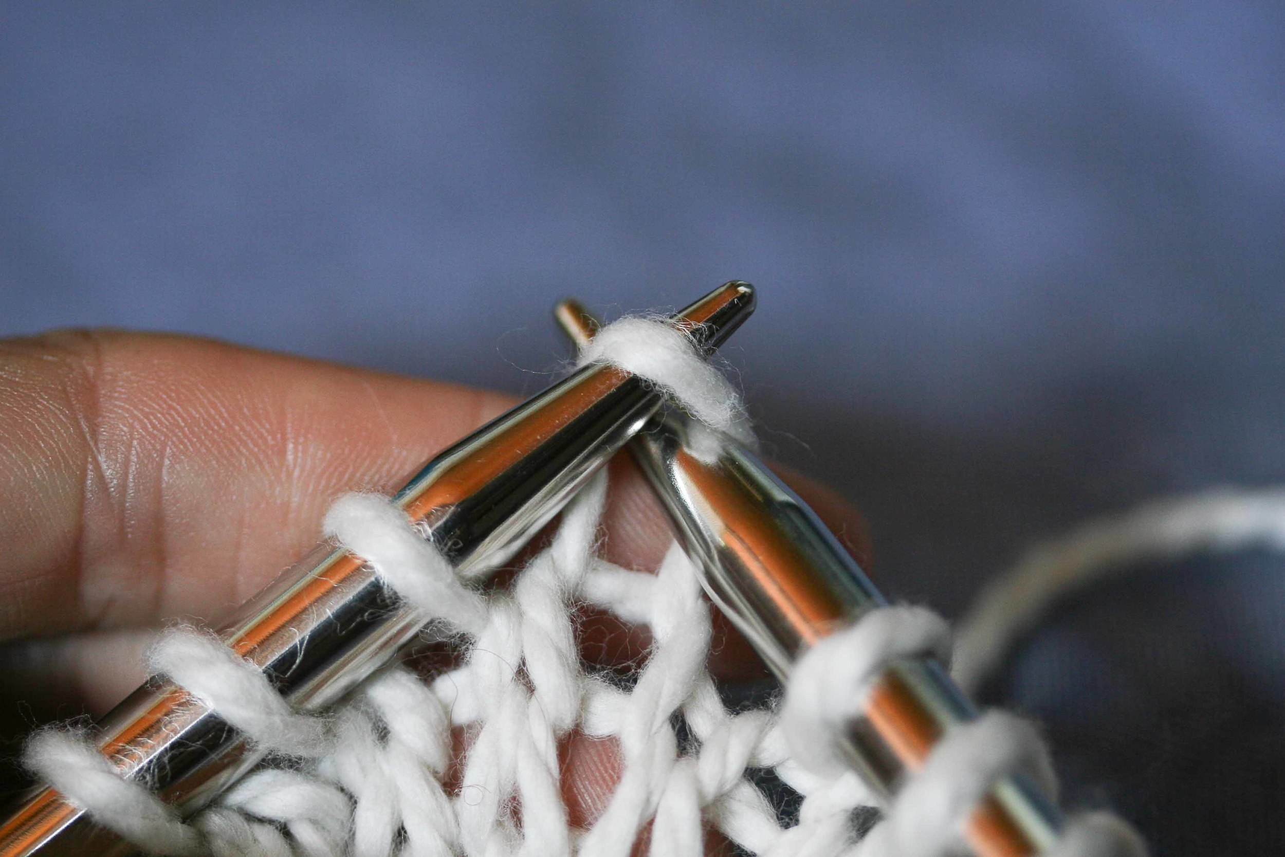 The right hand side of the stitch is on the front of the needle.