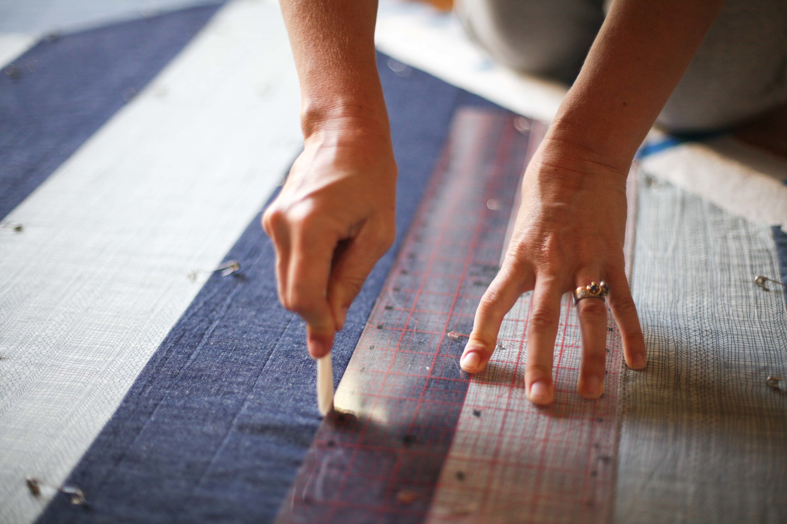 The linen/cotton mix of the denim stripe has a more fixed structure - so two corners of the quilt have straight lines.