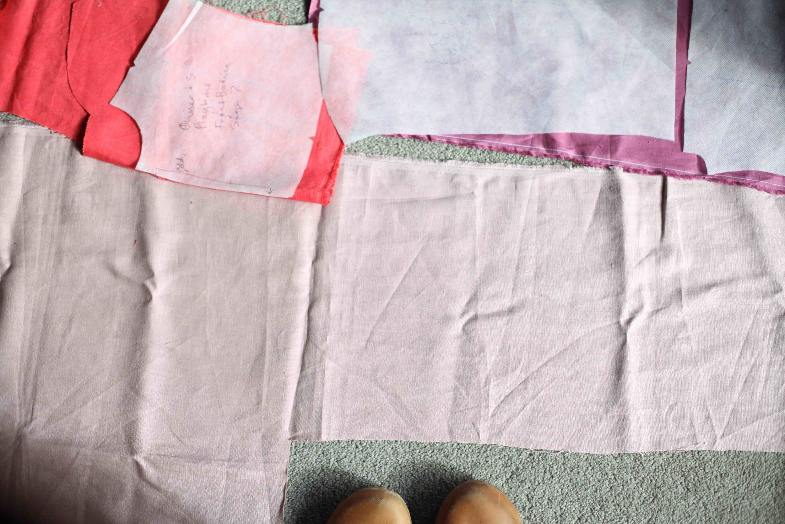 A photo of me trying to get all the pattern pieces to fit onto my scraps to make a scrap dress. You can see what the front turned out like below. One sleeve of the frock will be the light pink and the other the dark pink.