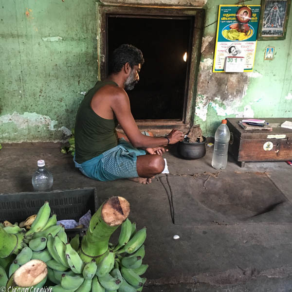 Lighting a cow dung fire to put with bananas in the 'banana cave' to ripen them Madurai Banana Market