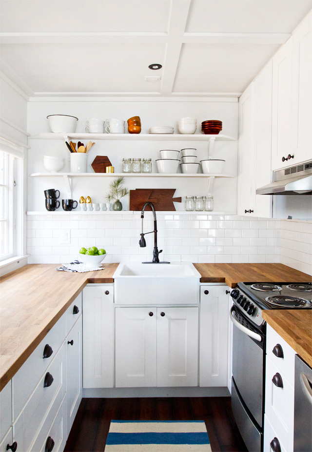 a clean classic kitchen with white cabinets, white subway tile and butcher block countertops via  Smitten Studio