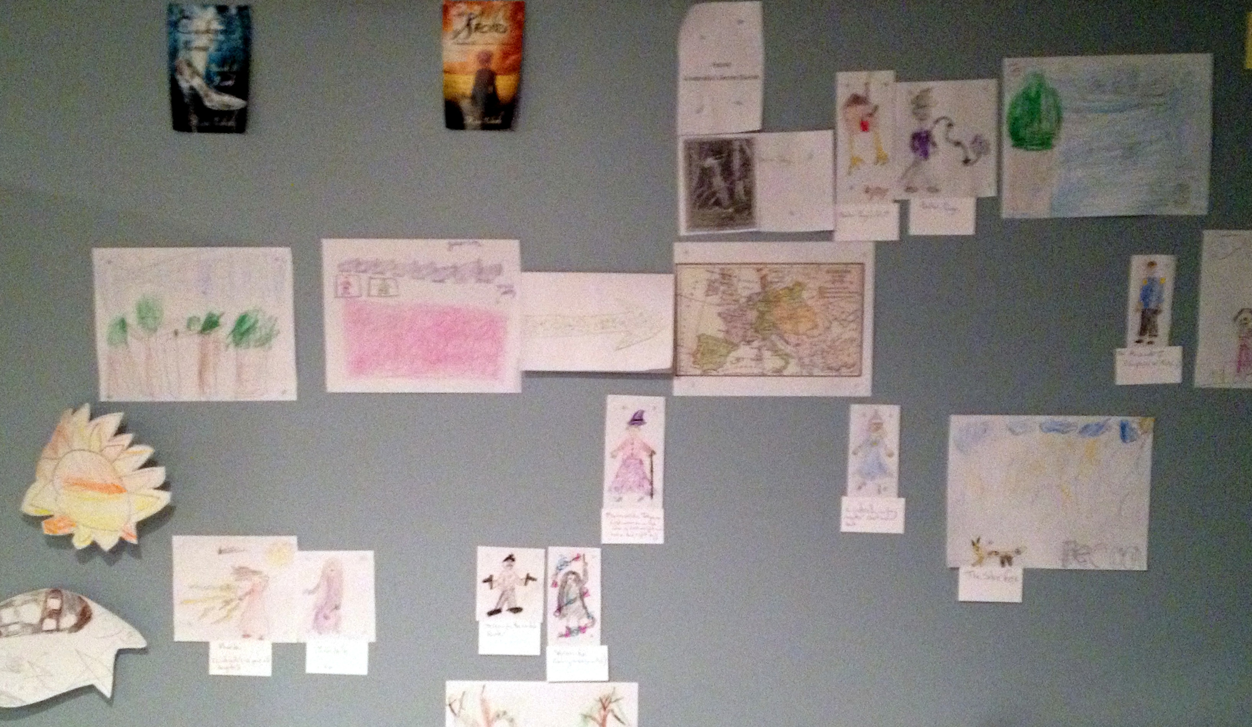 My kids' artwork and interpretation of characters in my book on my bedroom wall.