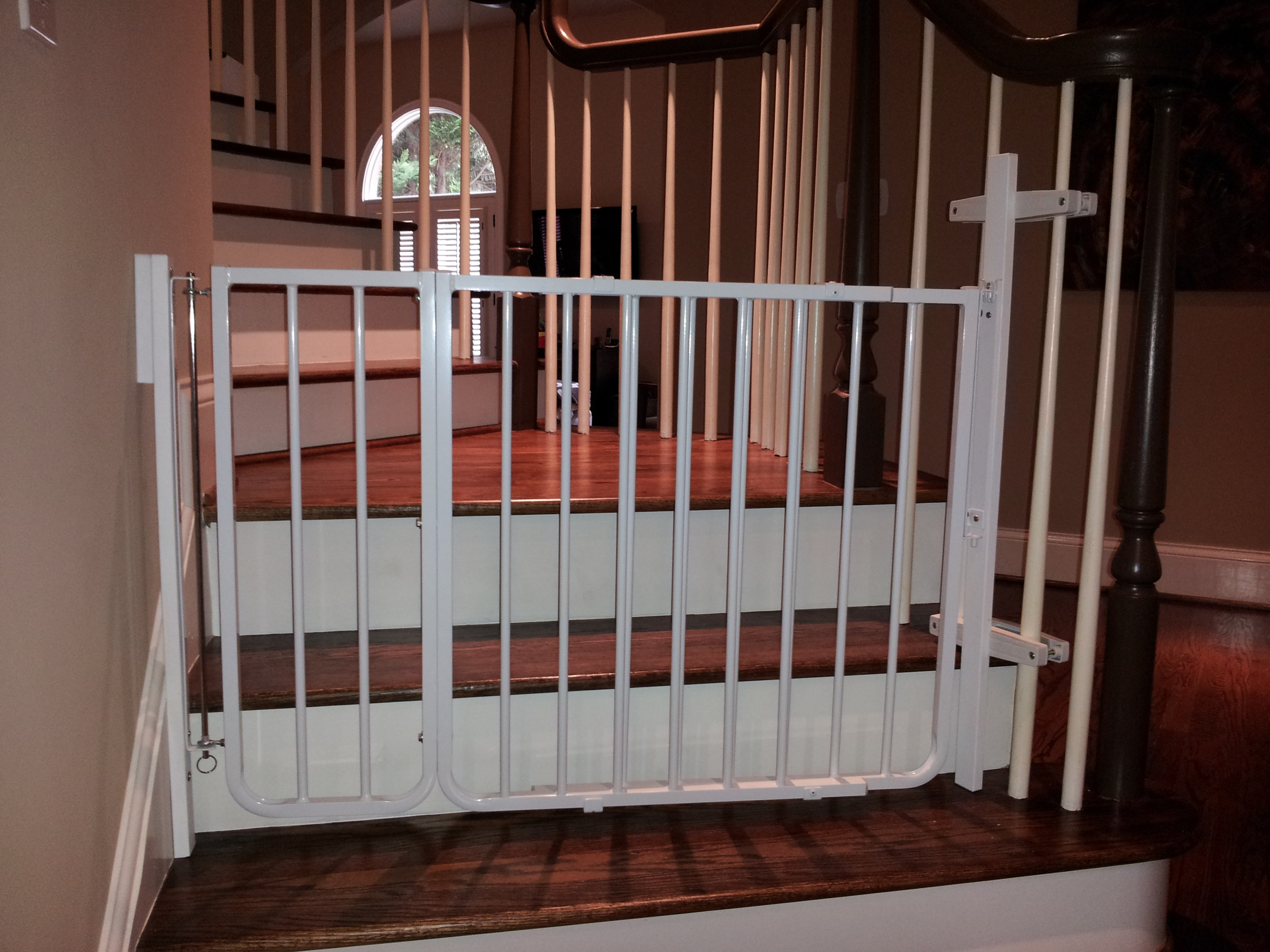 Stair gate installed using non-damaging spindle post bracket and extension for wide width