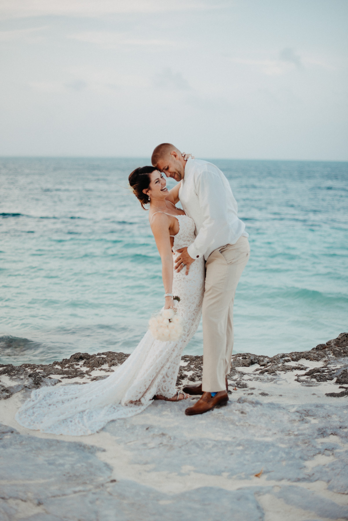 Julia and Tony, in front of the beautiful blue waters off the coast of Cancun, Mexico, in Riviera Maya, after their beach front wedding. They decided to have a destination elopement with their nearest and dearest in Cancun. I can only imagine I had a super lame dad joke here, which is why they are laughing! Copyright: Teresa Woodhull Photography