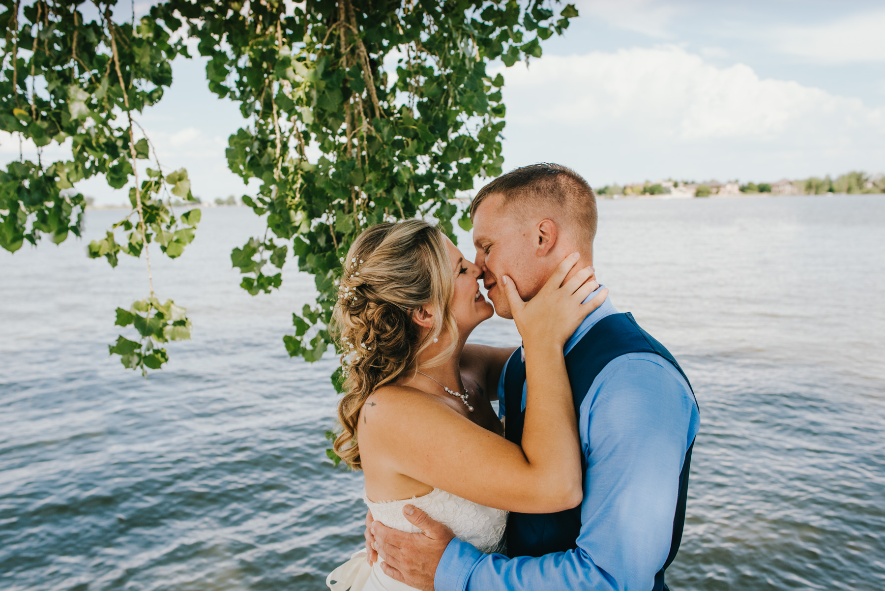 Jessi and Dan got married at her parents Boyd Lake lakehouse over the summer. They property, which is right outside of Fort Collins, made for a gorgeous lakefront destination wedding. I love the way the green trees are hanging low just behind Jessi and Dan. This is a moment I captured shortly after their first look on the lake. Copyright: Teresa Woodhull Photography