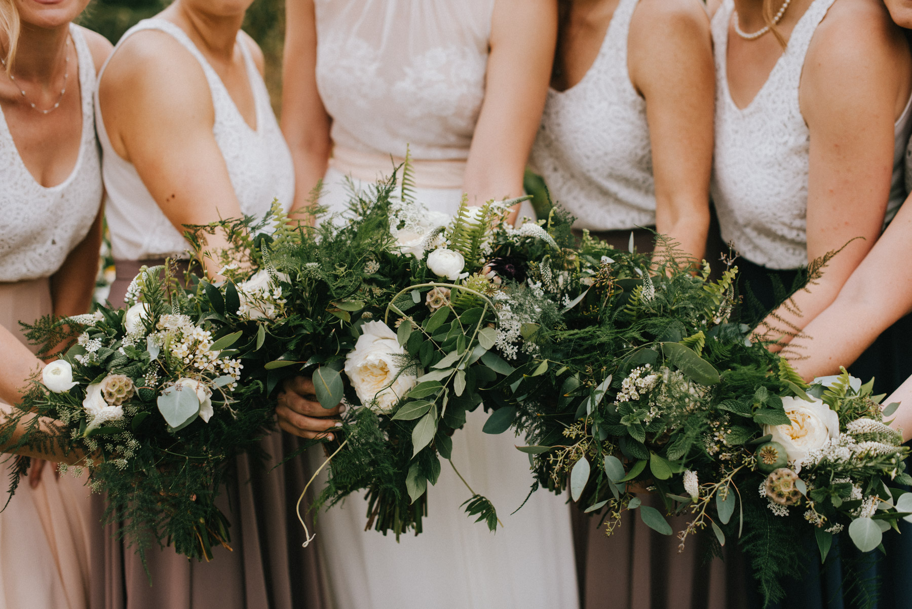 Lindsey and her bridesmaids bouquets on her wedding day at Hudson Gardens in Littleton, Colorado. Her flowers included a mix of eucalyptus pods, lots of greenery and white flowers.