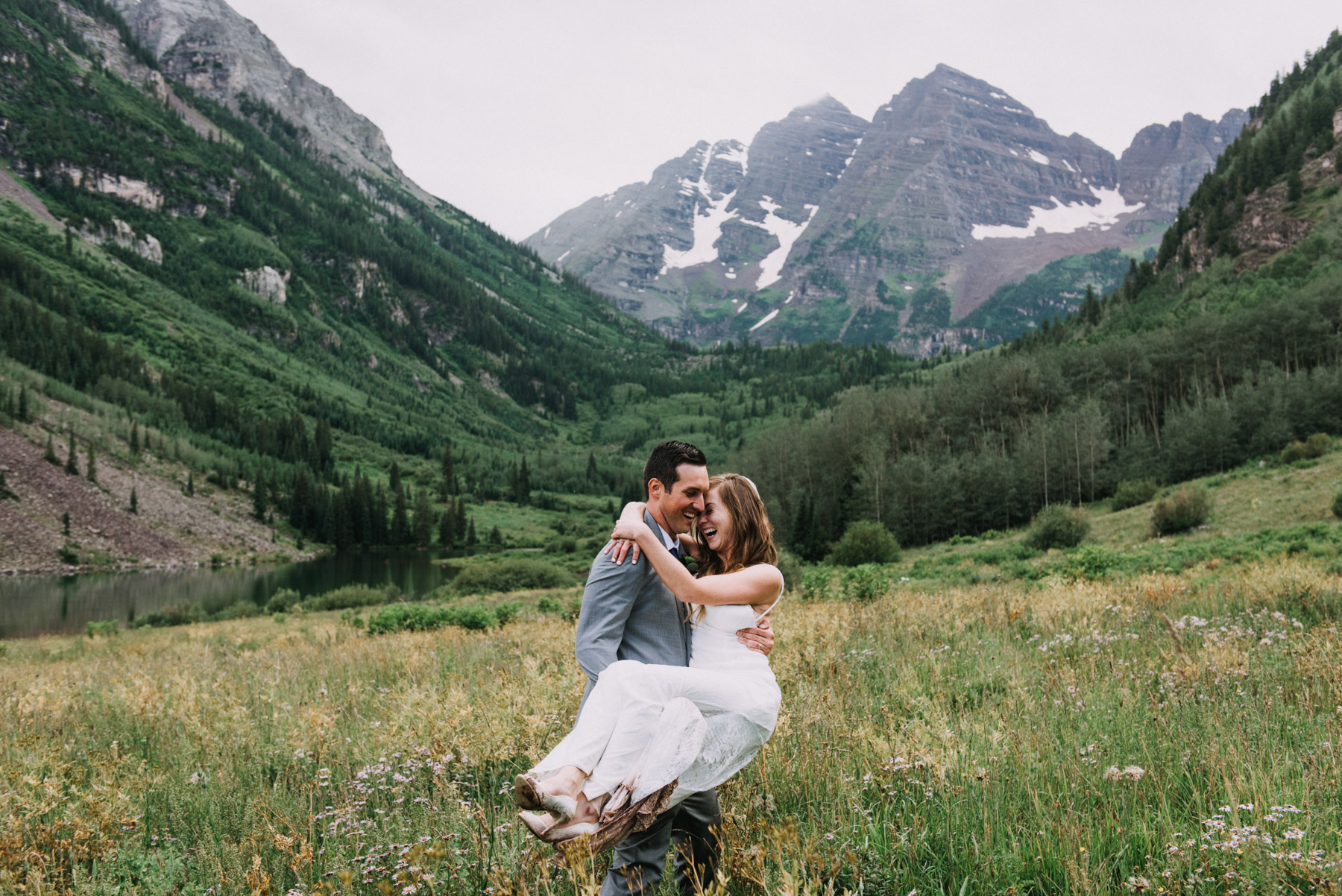 Heather and Darron were all about hiking through the mud after their Maroon Bells elopement ceremony. They decided against the big wedding and felt it was more them to have a let's elope to Aspen kind of wedding. They stood in front of the Maroon Bells while they said I do. Here they are laughing during their mountain bride and groom portraits. The Maroon Bells is definitely one of my favorite destination elopement spots!