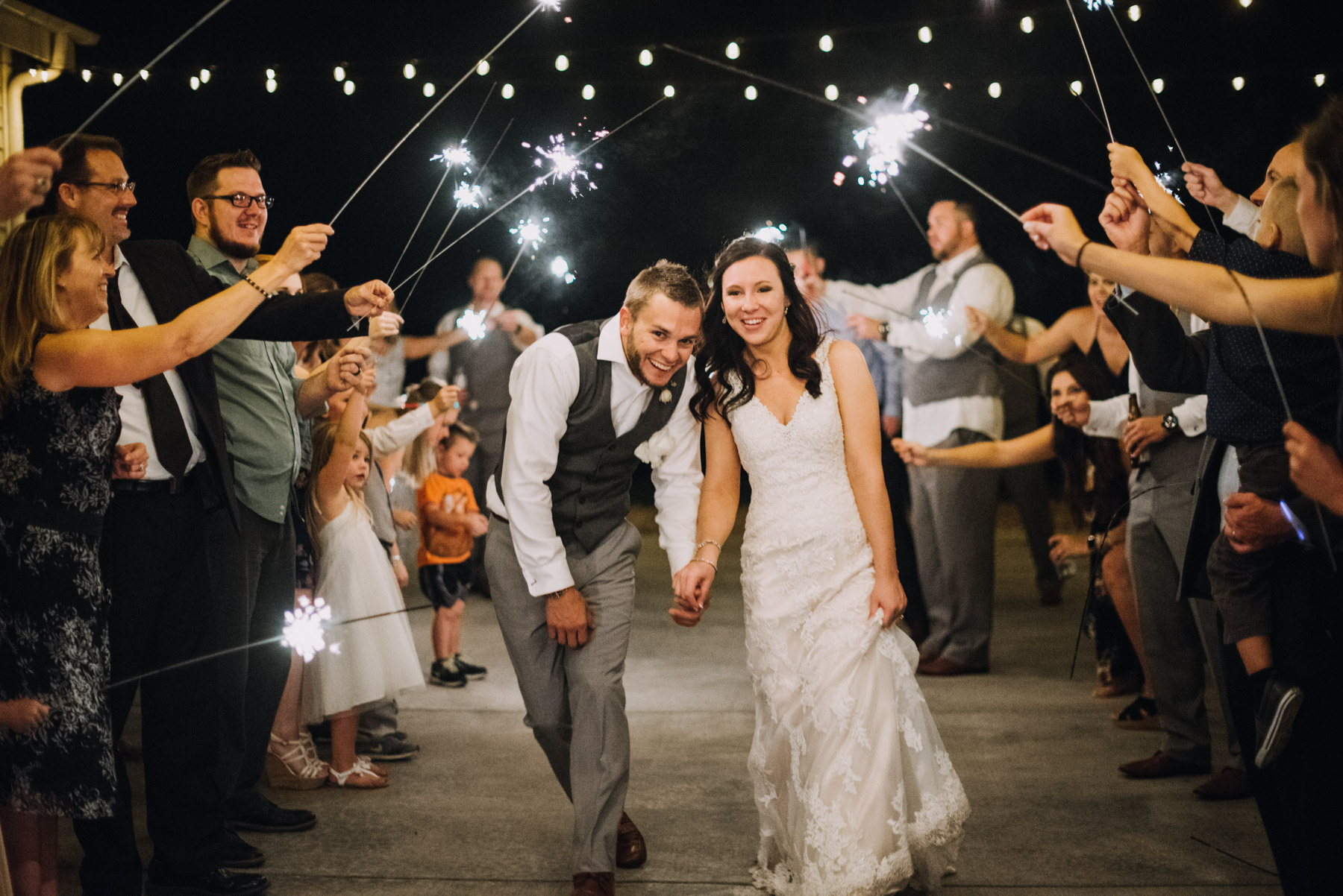 Chris and Lynsey running down between their friends for a sparkler exit at their Flying Horse Ranch Wedding!