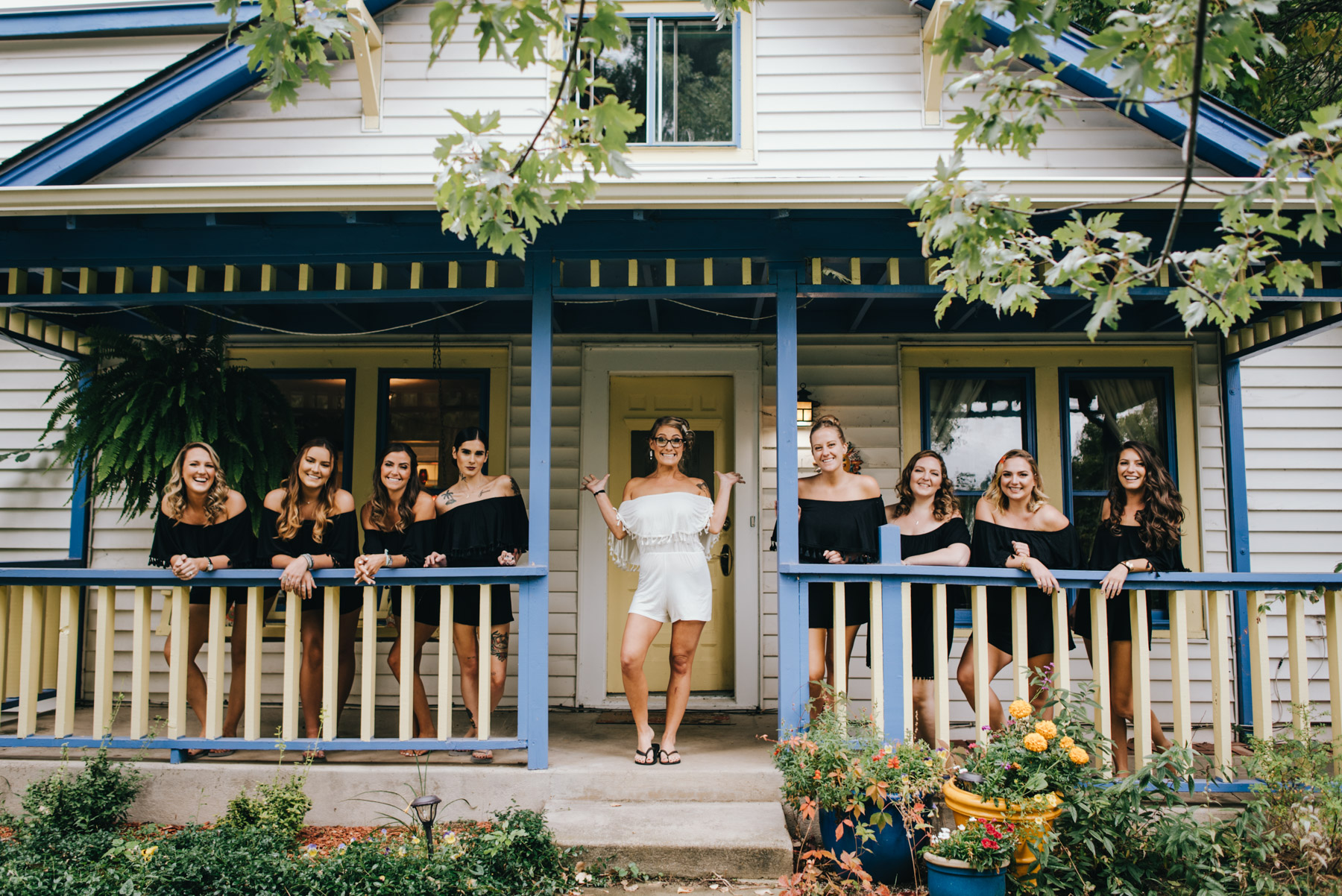 Alexa and her bridesmaids on the porch at the Kelly Urban Farm. The blue and yellow porch is a fun spot to take all kinds of photos, including these of the girls while they were getting ready. I love the realness of how Alexa still has curlers in her hair, and the girls are all still in the black off shoulder rompers Alexa gave each girl as a bridesmaids gift.