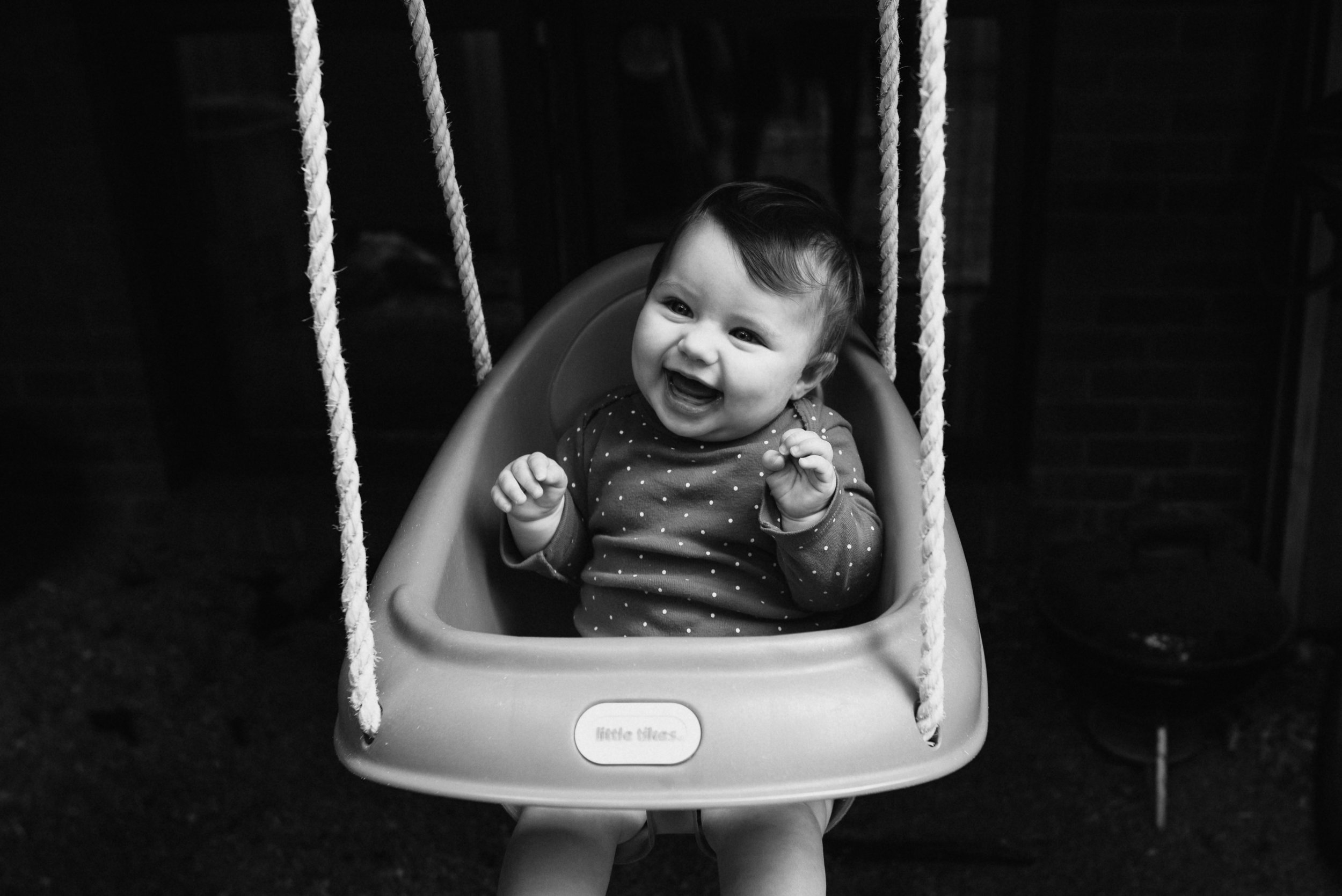 My daughter Luna at 7 months old, loving her first swing.