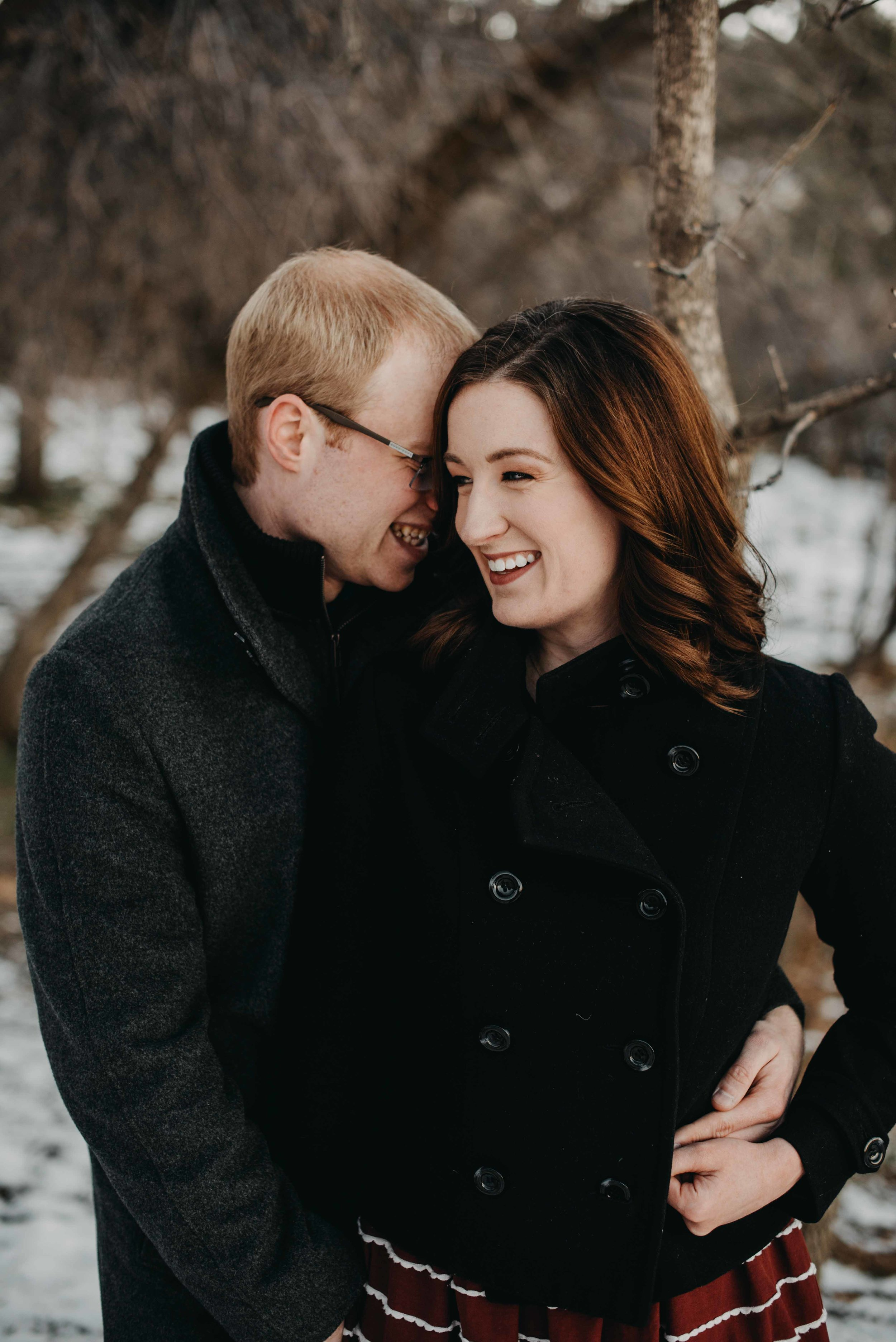 Peter hugging Trinity during their snowy engagement session in Boulder, Colorado. We met in Chautauqua for some fun hiking in the snow photos.