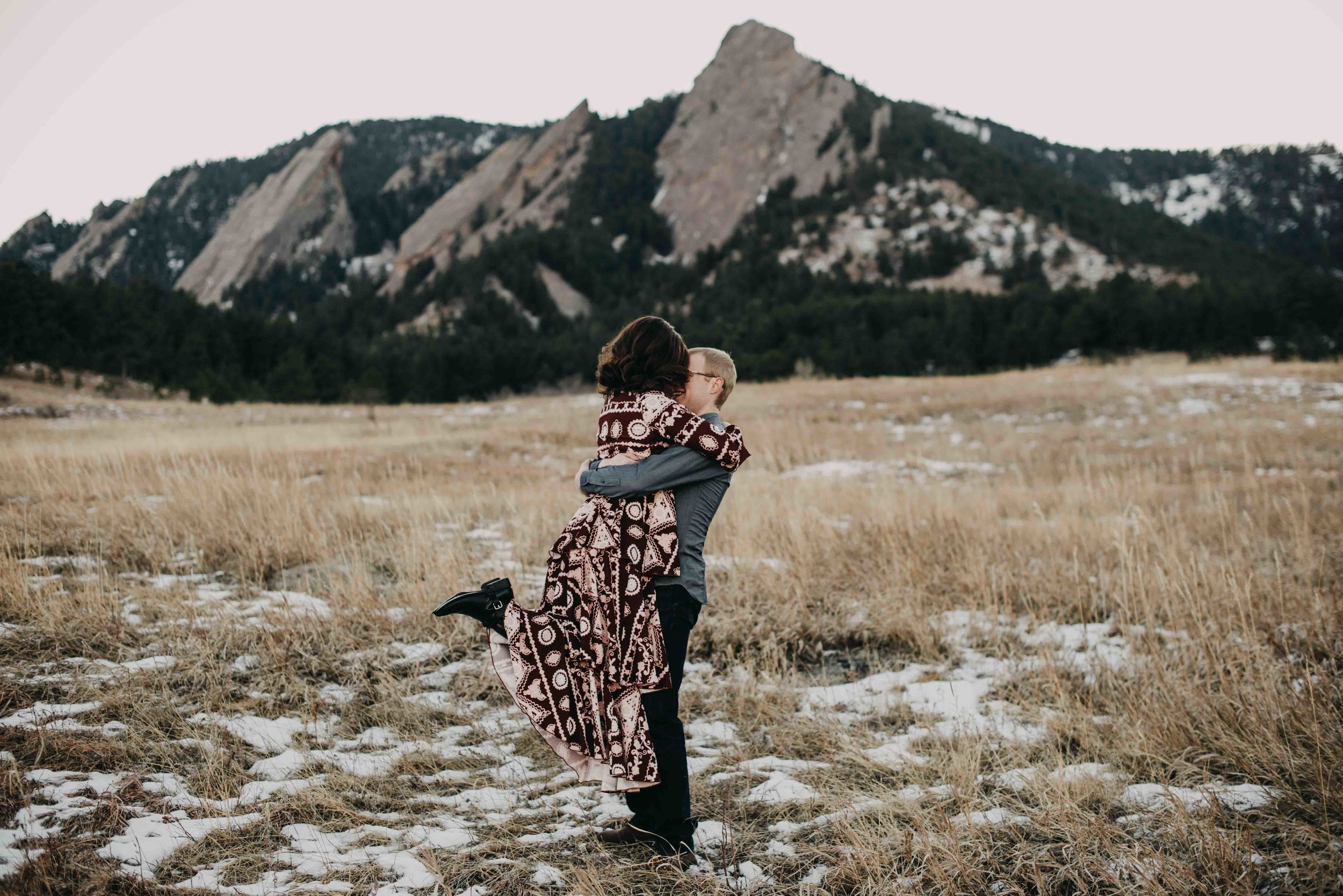 Trinity and Peter embracing in front of the flatirons during their Chautauqua Engagement Session.