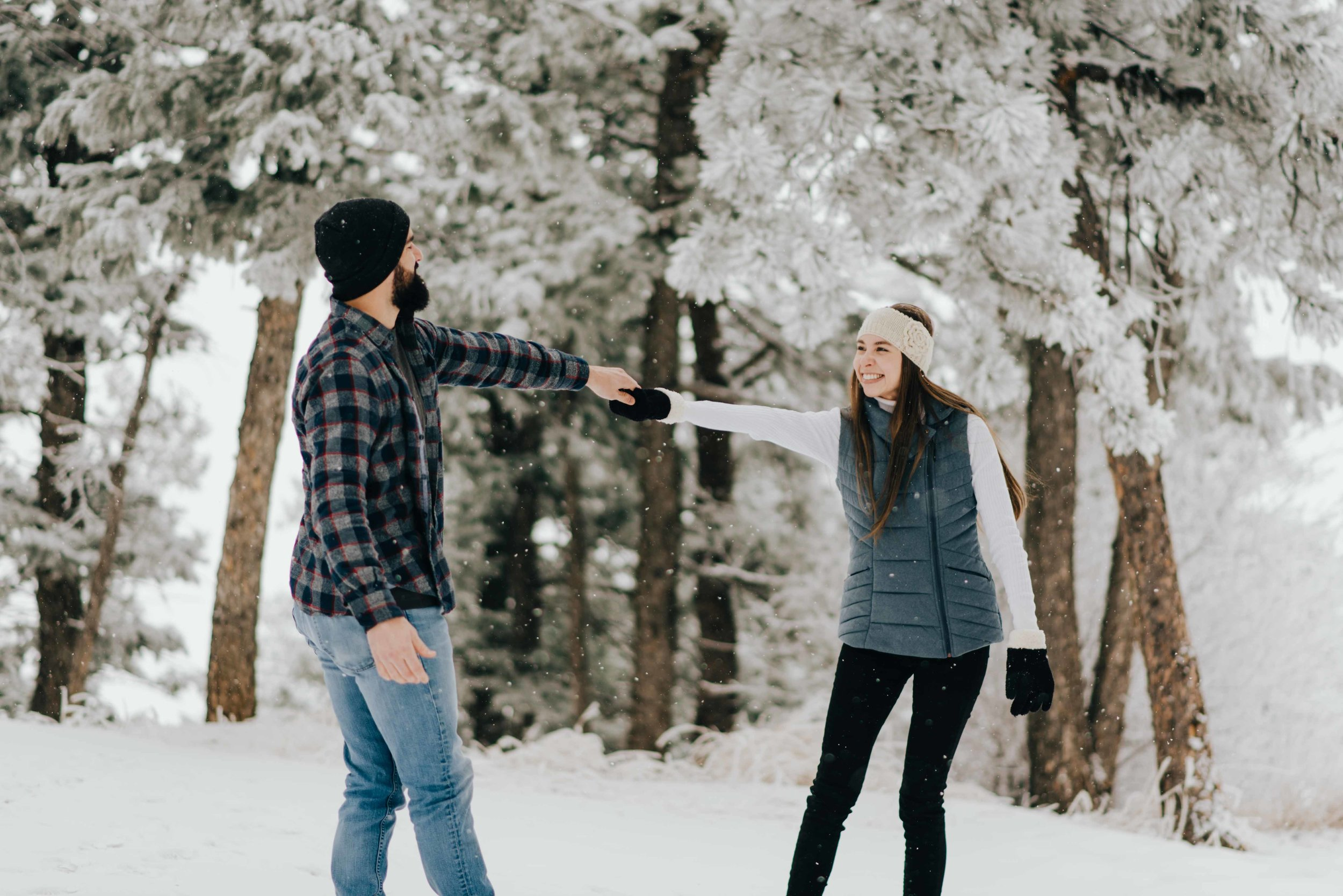 Tani and Nik dancing in the snow during their snowy engagement session in Golden, Colorado.