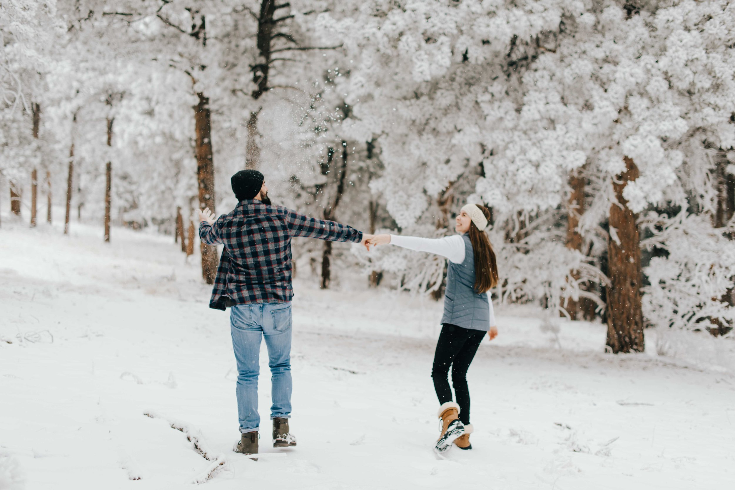 Nik and Tani playing in the snow during their mountain engagement session in Golden, Colorado. The weather was cold and snowy, but they totally embraced it!