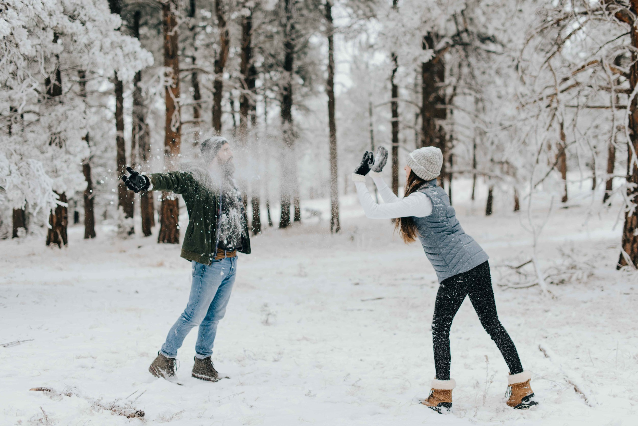 Nik and Tani engaging an an epic snowball fight during their mountain engagement session in Colorado.