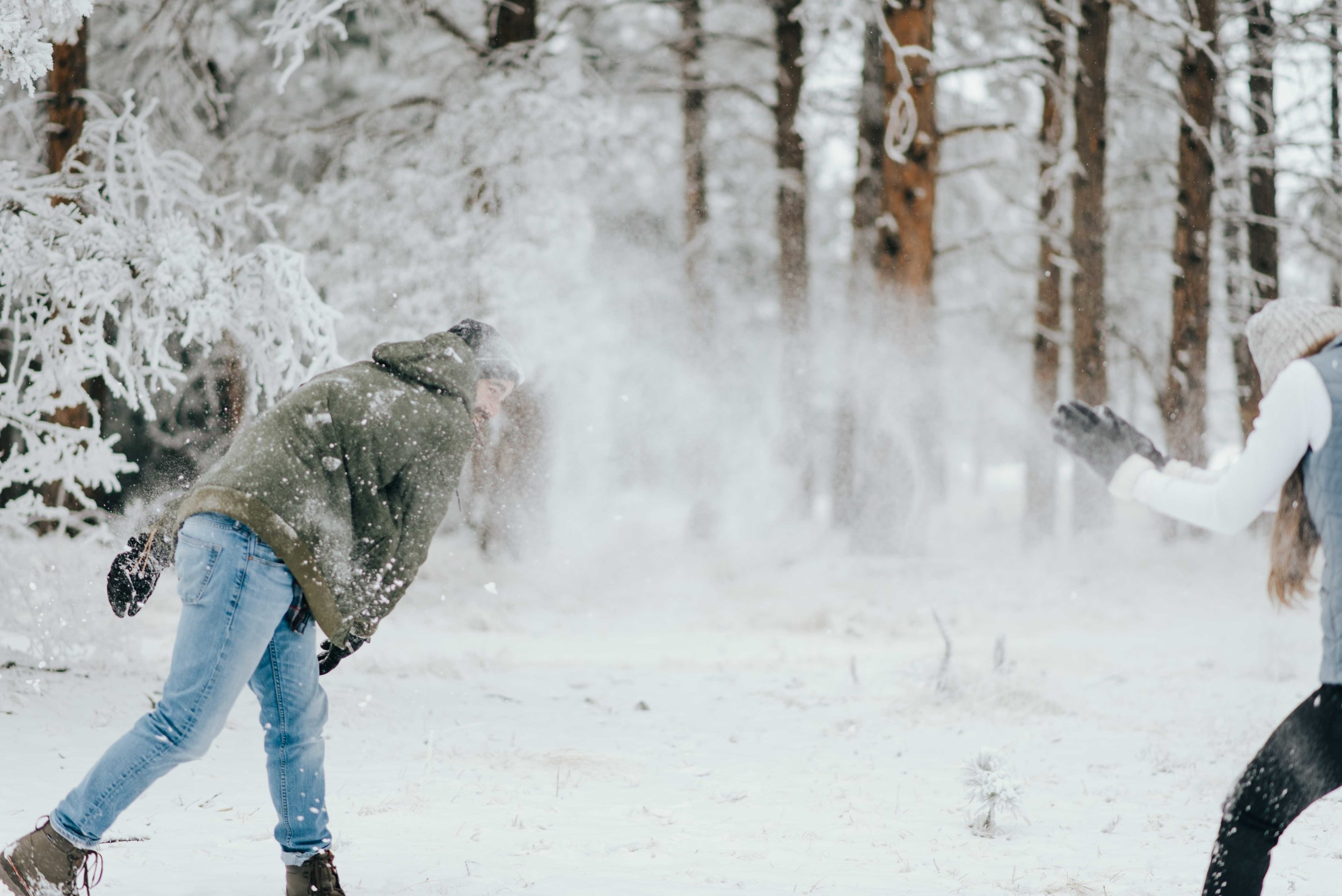 Nik and Tani fighting it out with snowballs during their snowy mountain engagement session in Colorado.