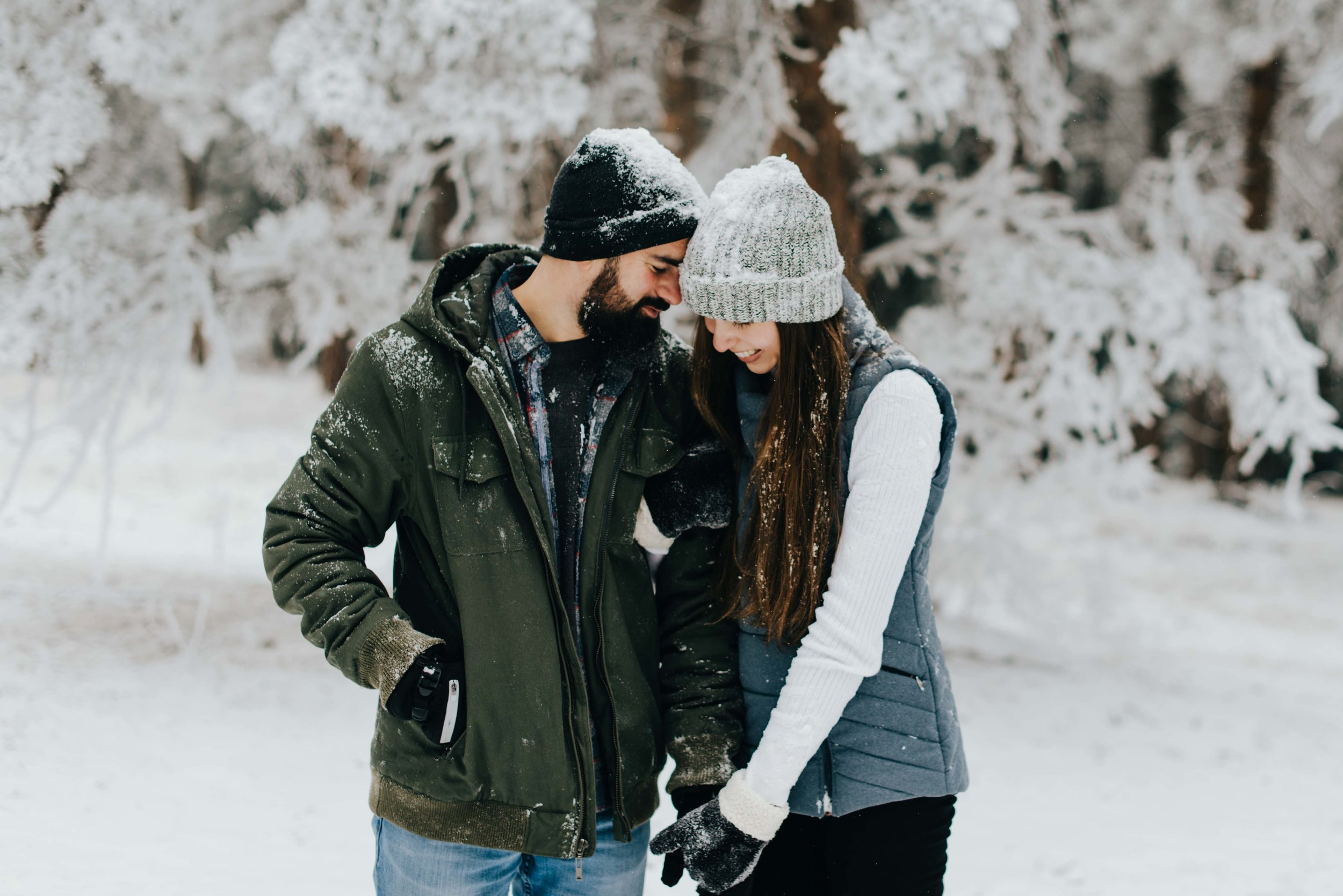 Nik and Tani meeting a truce after their snowball fight. Here they are holding hands during their adventurous engagement session.