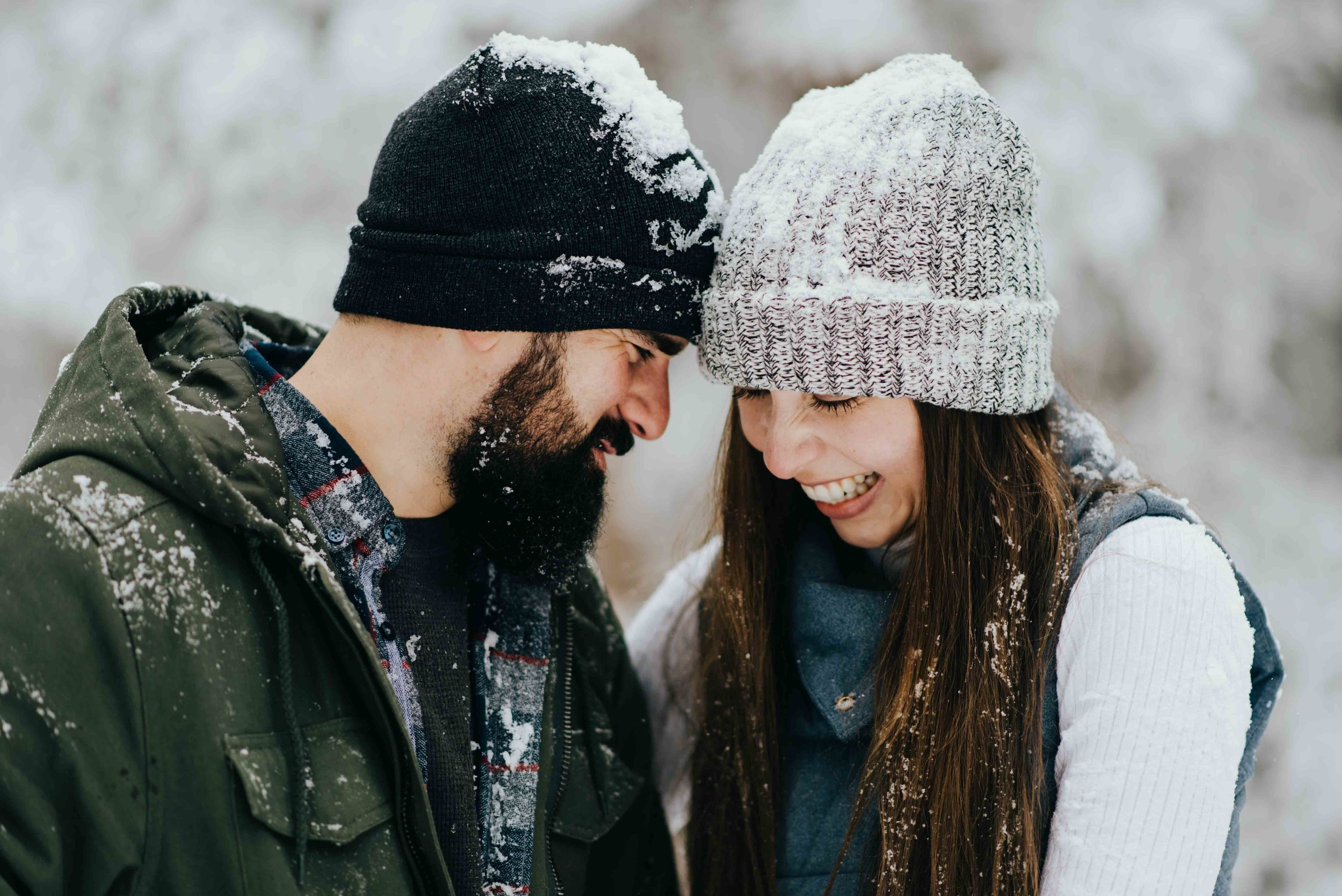 Tani and Nik cuddling during their snow-filled engagement session in Colorado.