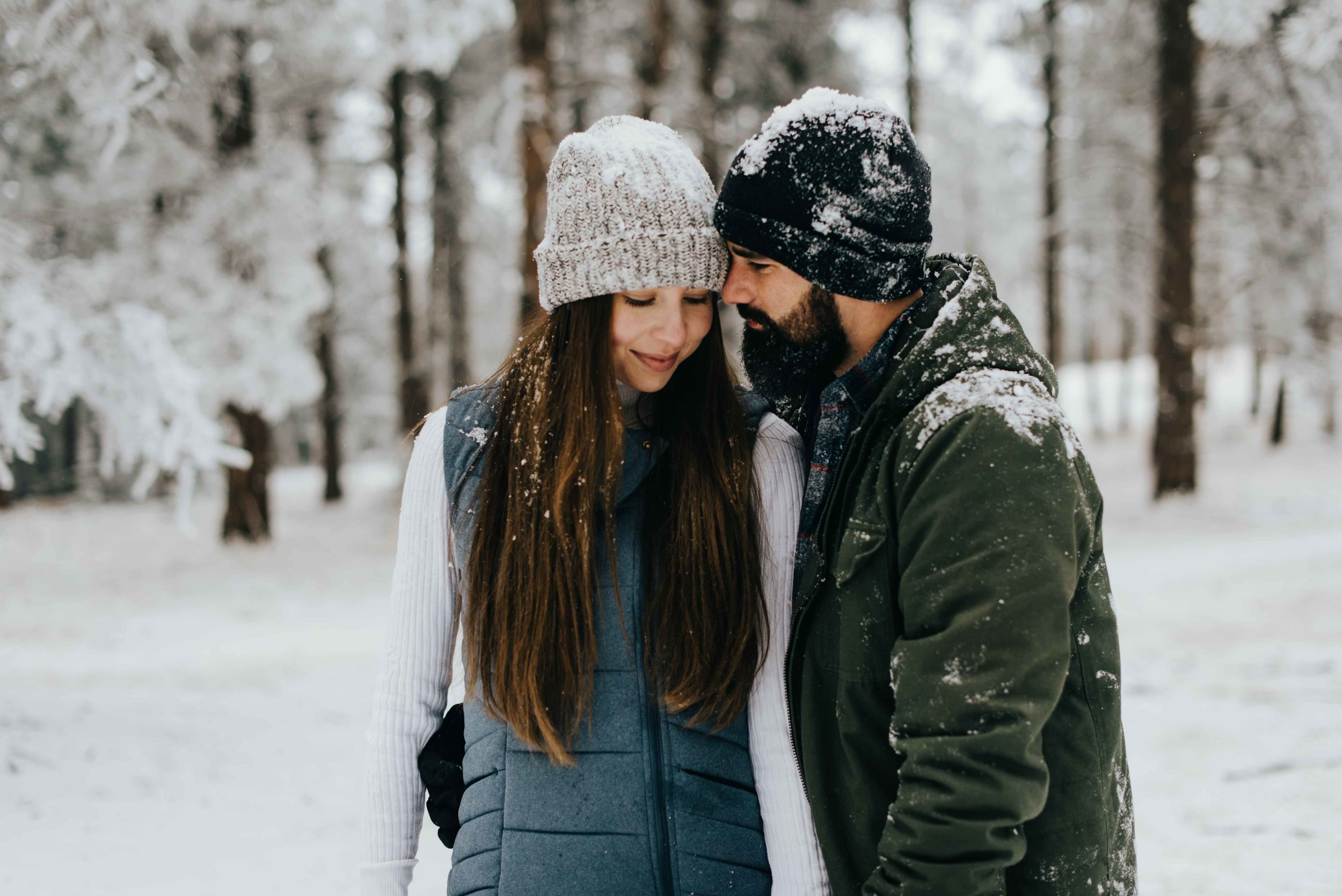 Nik holding Tani during their snowy engagement session.