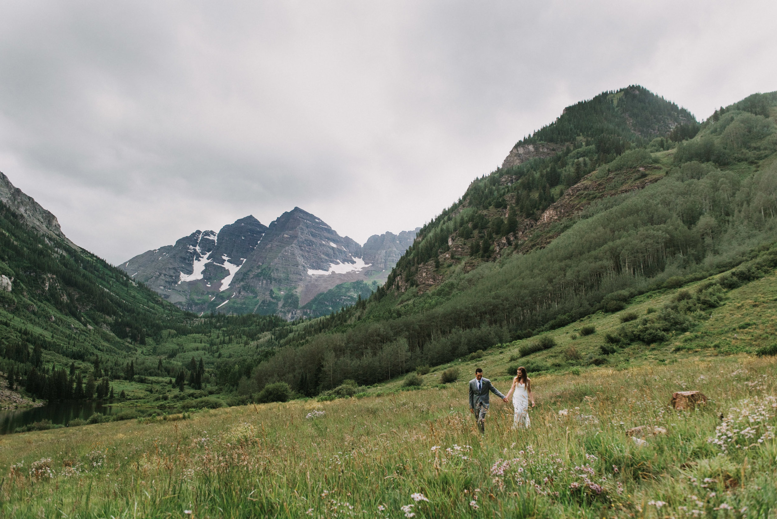 Heather and Darren walking through a field in front of the Maroon Bells.